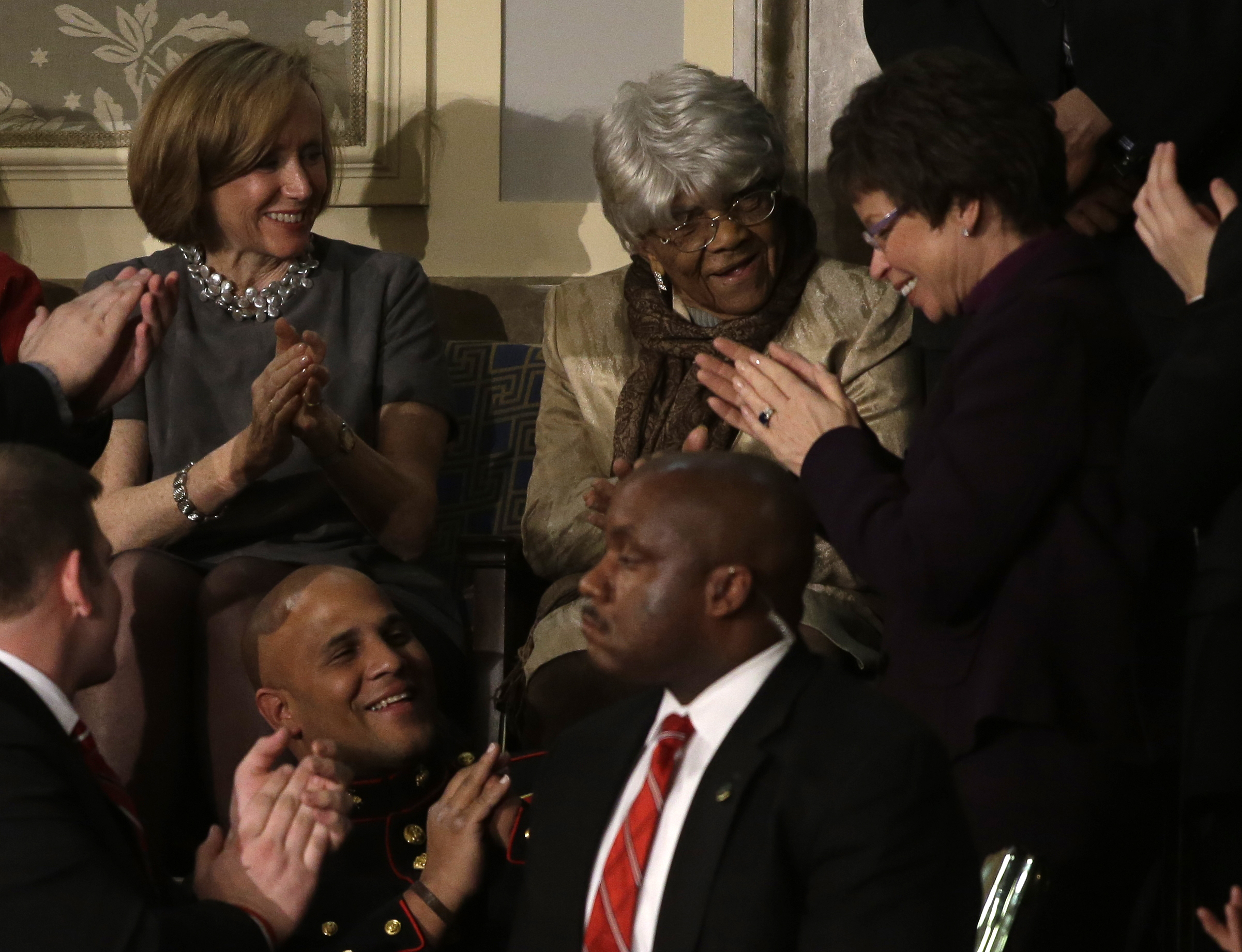 """Desiline Victor, 102, of Miami is applauded by White House senior adviser Valerie Jarrett, right, and others, during President Barack Obama's State of the Union address during a joint session of Congress on Capitol Hill in Washington, on Feb. 12, 2013. Victor is being hailed as a champion voter after heading to her local polling place twice and waiting more than three hours in line to cast her vote. She was reportedly cheered by her fellow voters as she emerged from the polling place, her """"I Voted"""" sticker firmly in hand. """"I wanted to vote for my guy, my son, President Obama,"""" she told the Miami Herald."""