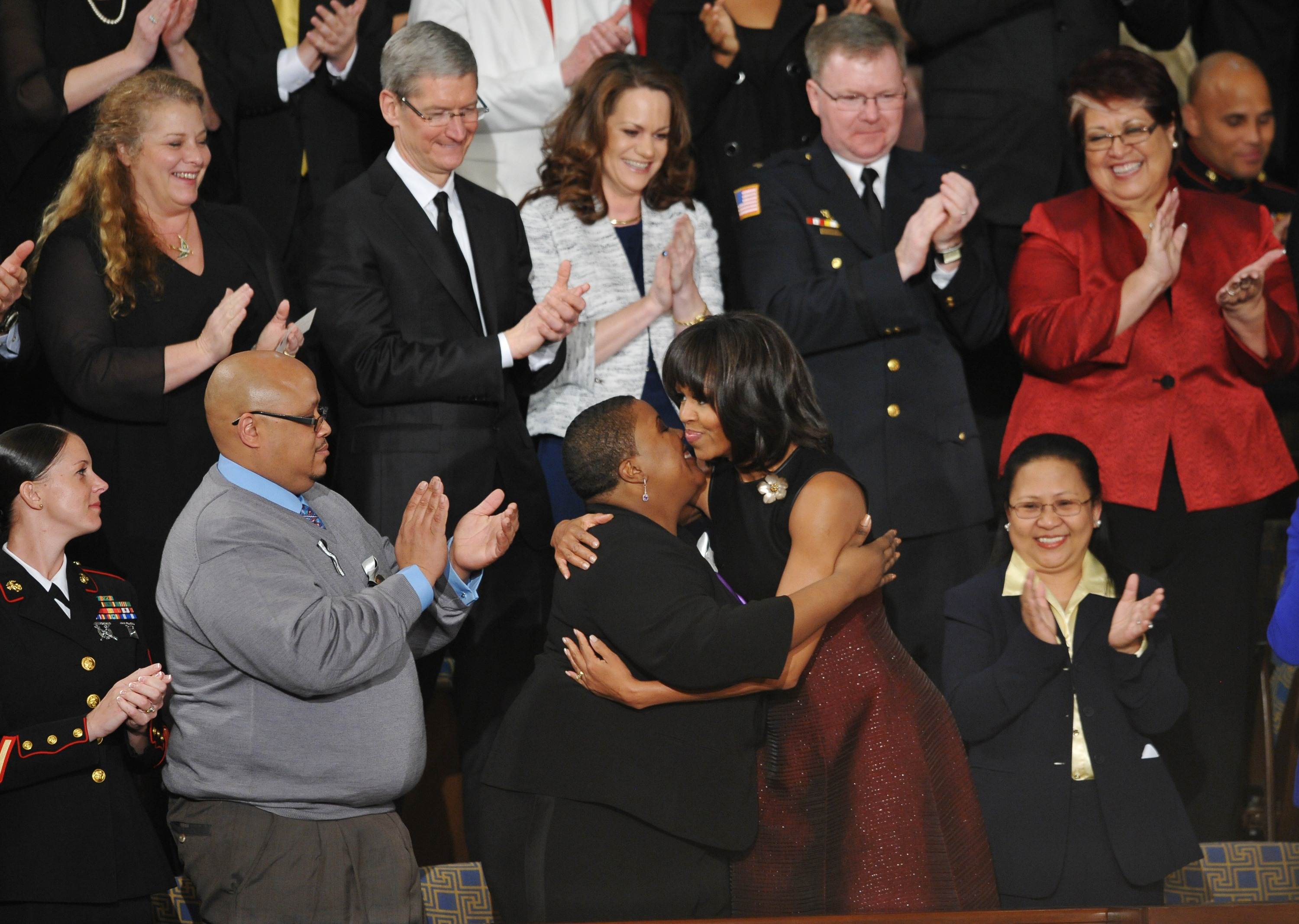 First Lady Michelle Obama hugs Cleopatra Cowley-Pendleton as Nathaniel A. Pendleton Sr., left, look on before the start ofthe State of the Union address before a joint session of Congress on Feb. 12, 2013 at the US Capitol in Washington, D.C. The Pendletons are the parents of Hadiya, a fifteen year-old who was gunned down in Chicago's South Side just days after she performed at Barack Obama's inauguration on Jan. 21.