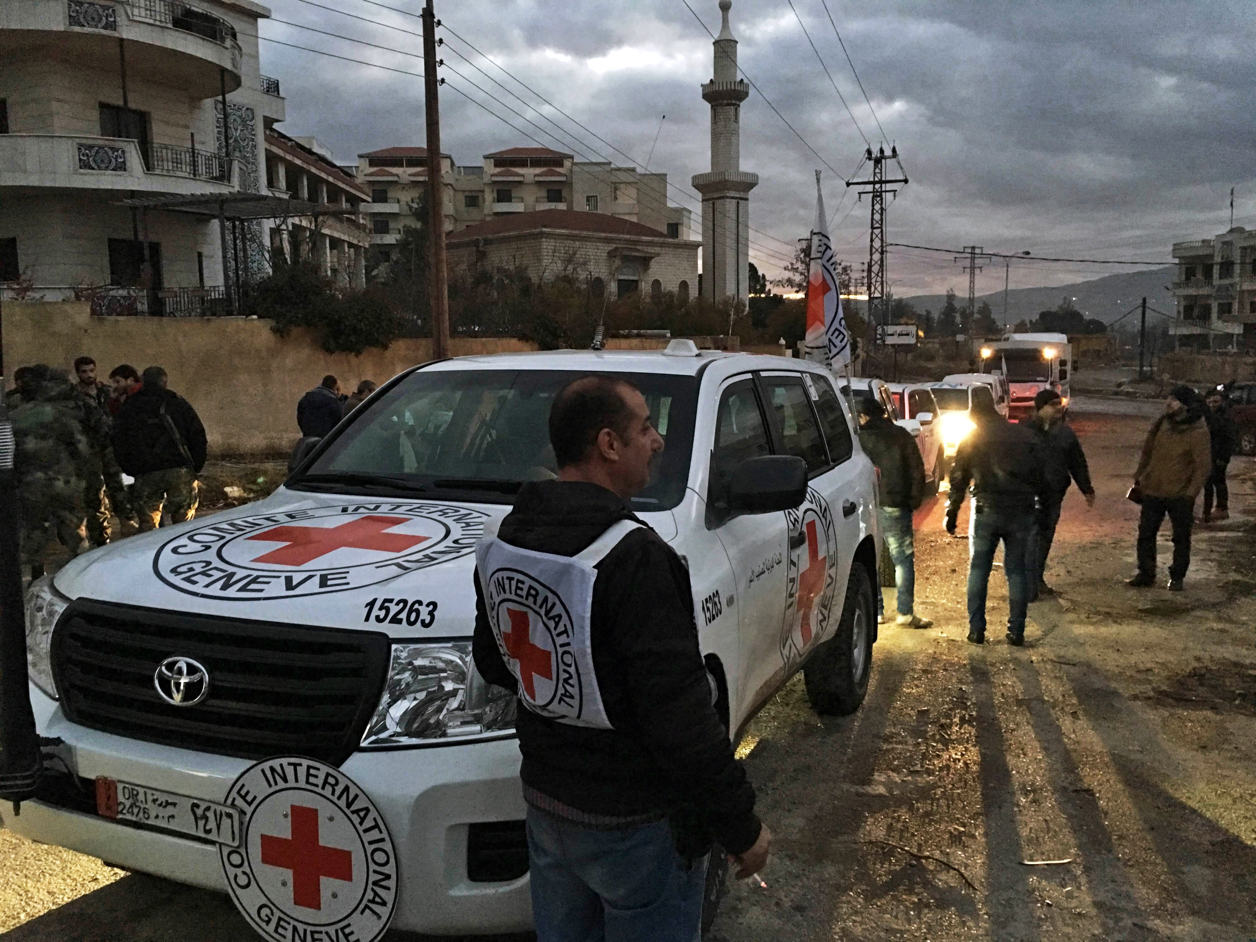 This Jan. 11, 2016 photo released by the International Committee of the Red Cross shows a Red Cross aid convoy upon its arrival at the besieged city of Madaya, Syria.