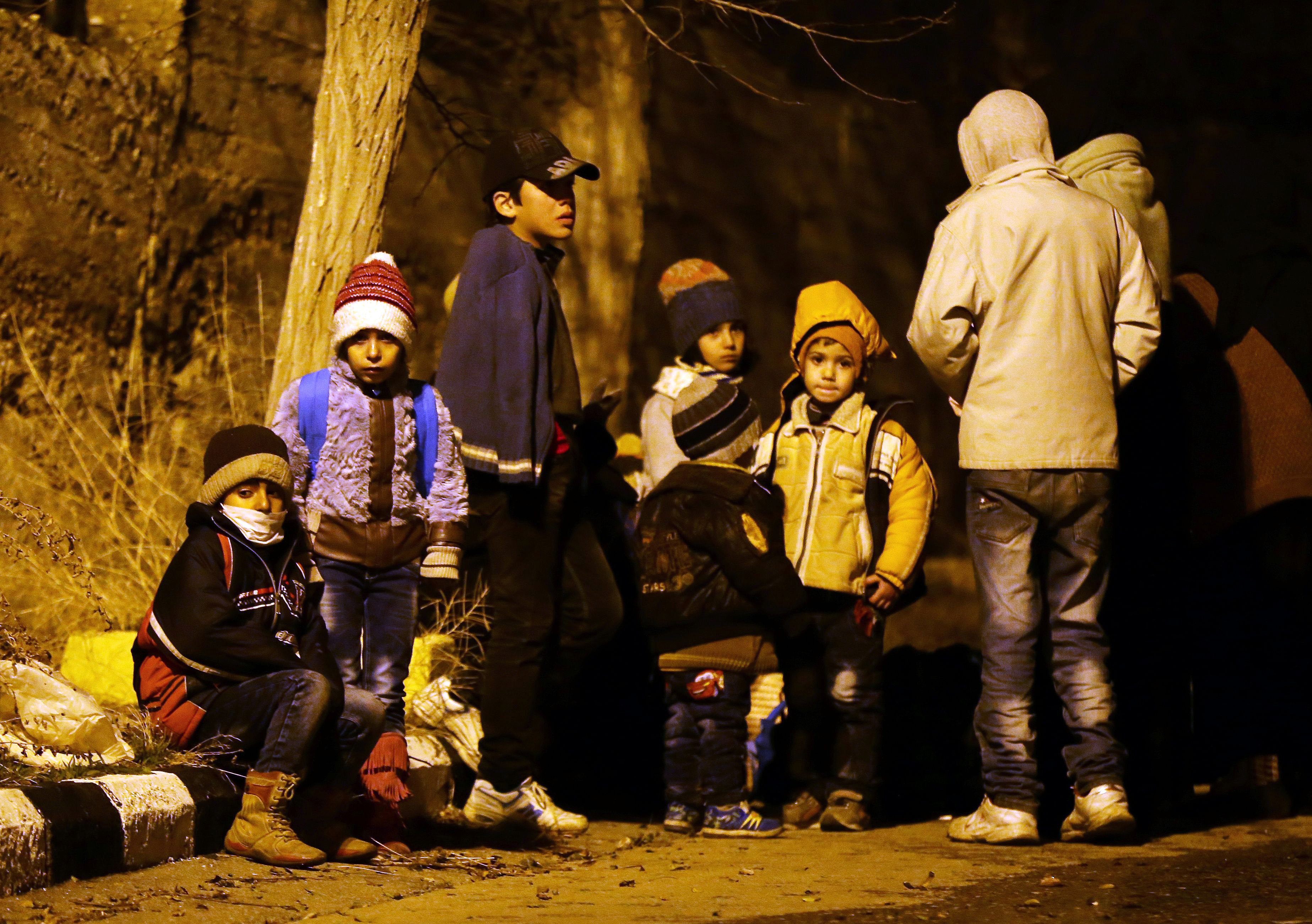 Syrian children wait on the outskirts of the besieged rebel-held Syrian town of Madaya, on January 11, 2016, after being evacuated from the town.