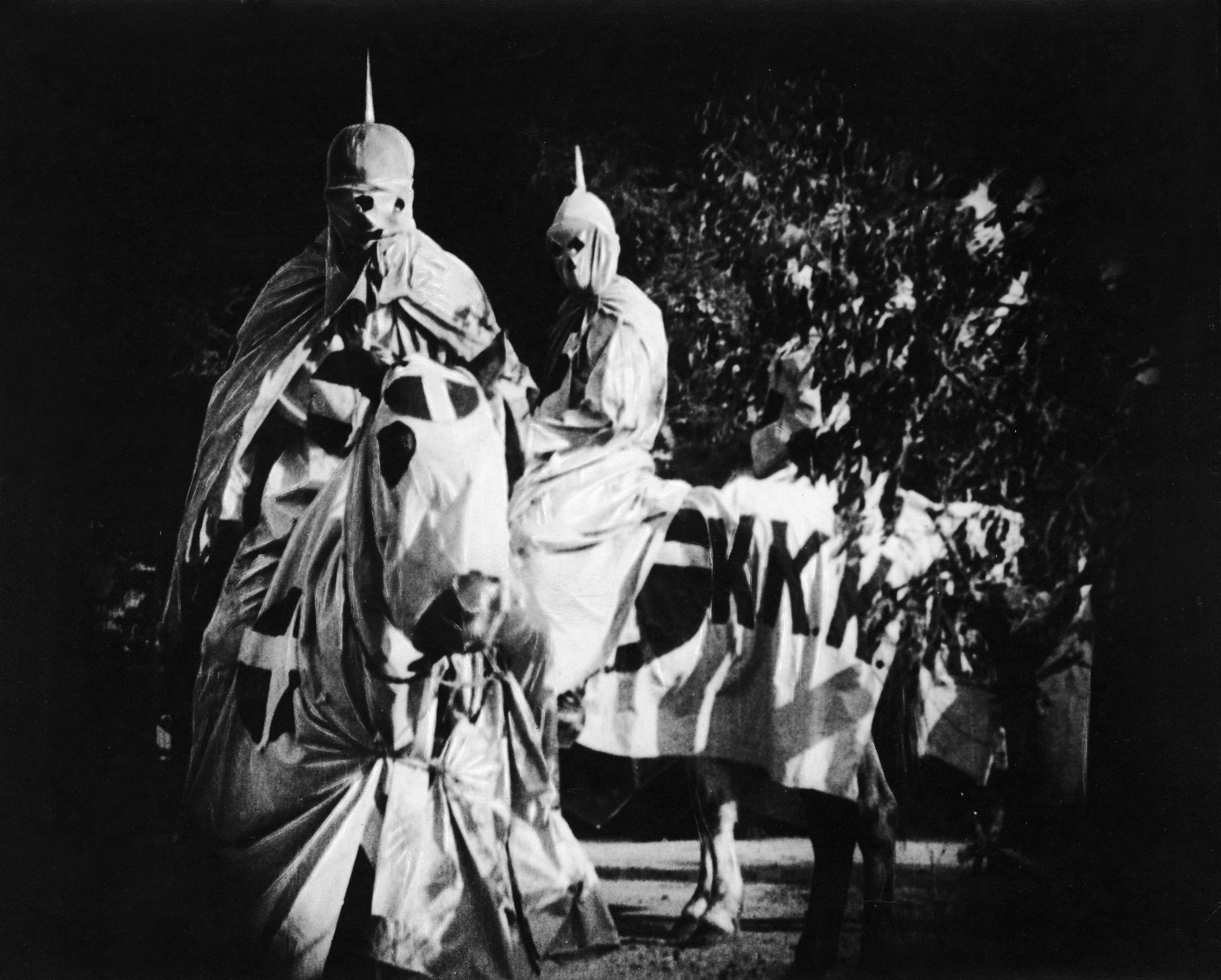 Actors costumed in the full regalia of the Ku Klux Klan ride on horses at night in a still from the 'The Birth of a Nation,' directed by D. W. Griffith, California, 1914.
