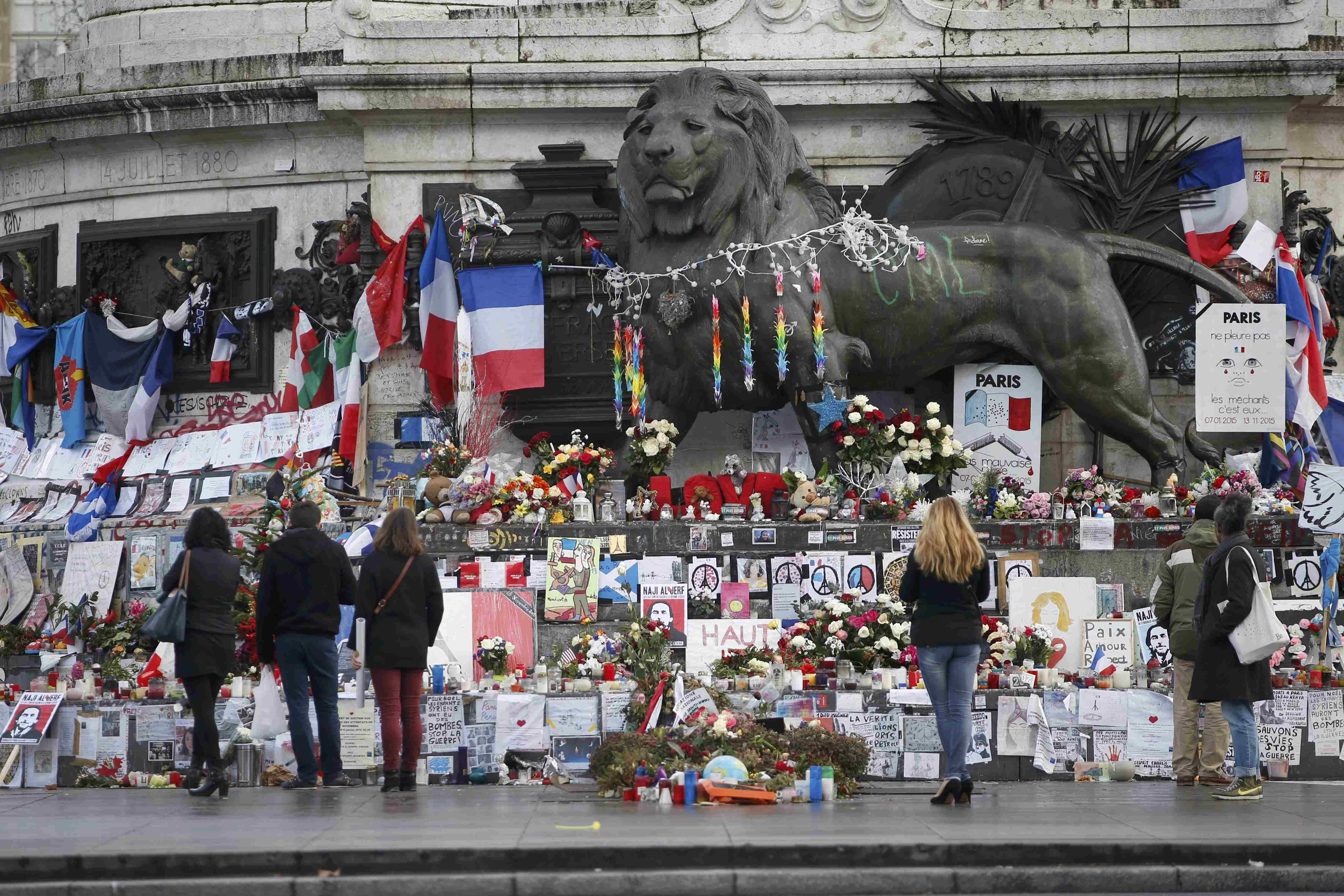 People look at flowers and messages to pay tribute to the victims of last year's January and November shooting attacks near the statue at the Place de la Republique in Paris on Jan. 6, 2016.