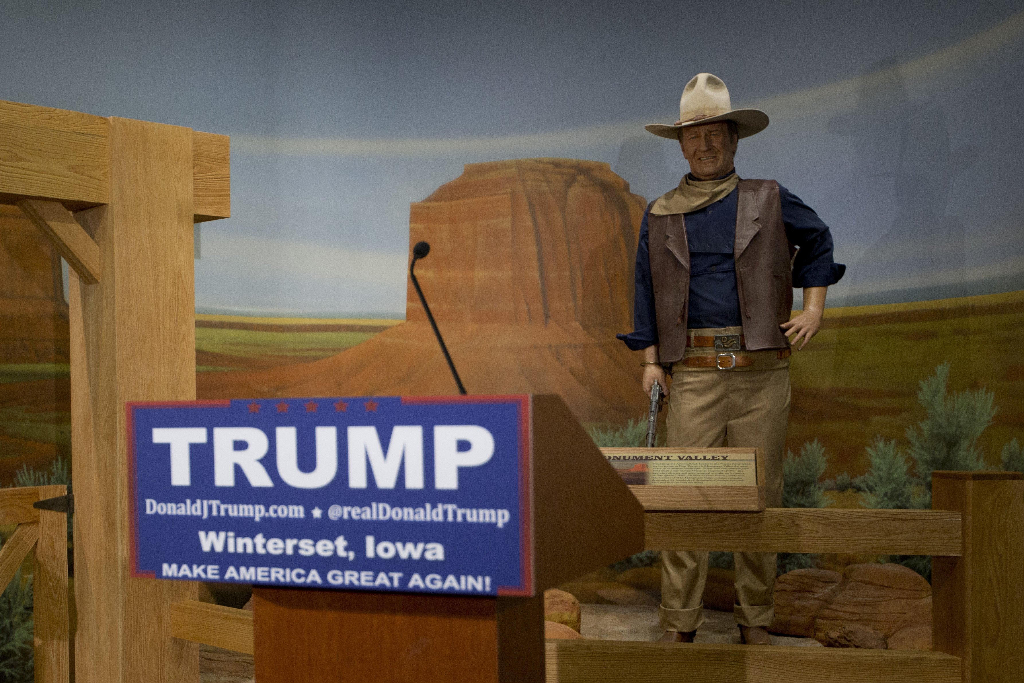 A podium for Donald Trump stands in front of a wax statue of John Wayne at the John Wayne Museum on Jan. 19, 2016, in Winterset, Iowa.