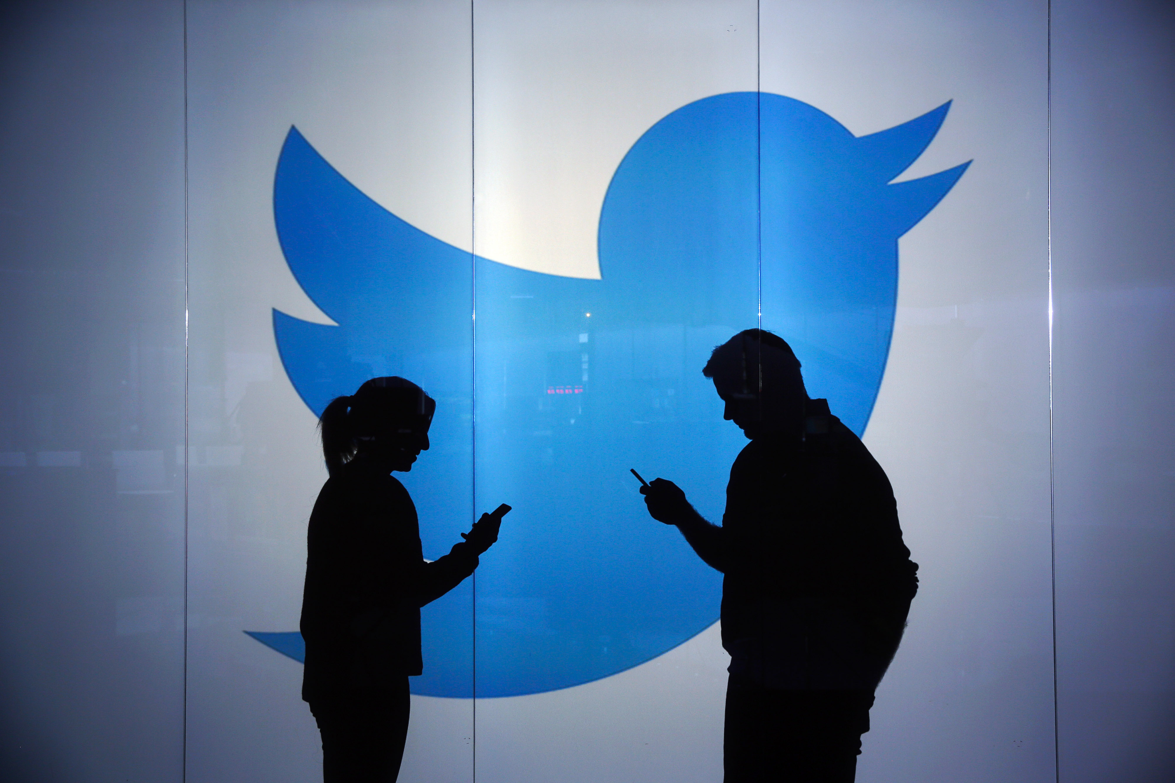 People are seen as silhouettes as they check mobile devices whilst standing against an illuminated wall bearing Twitter Inc.'s logo in London, U.K., Jan. 5, 2016.