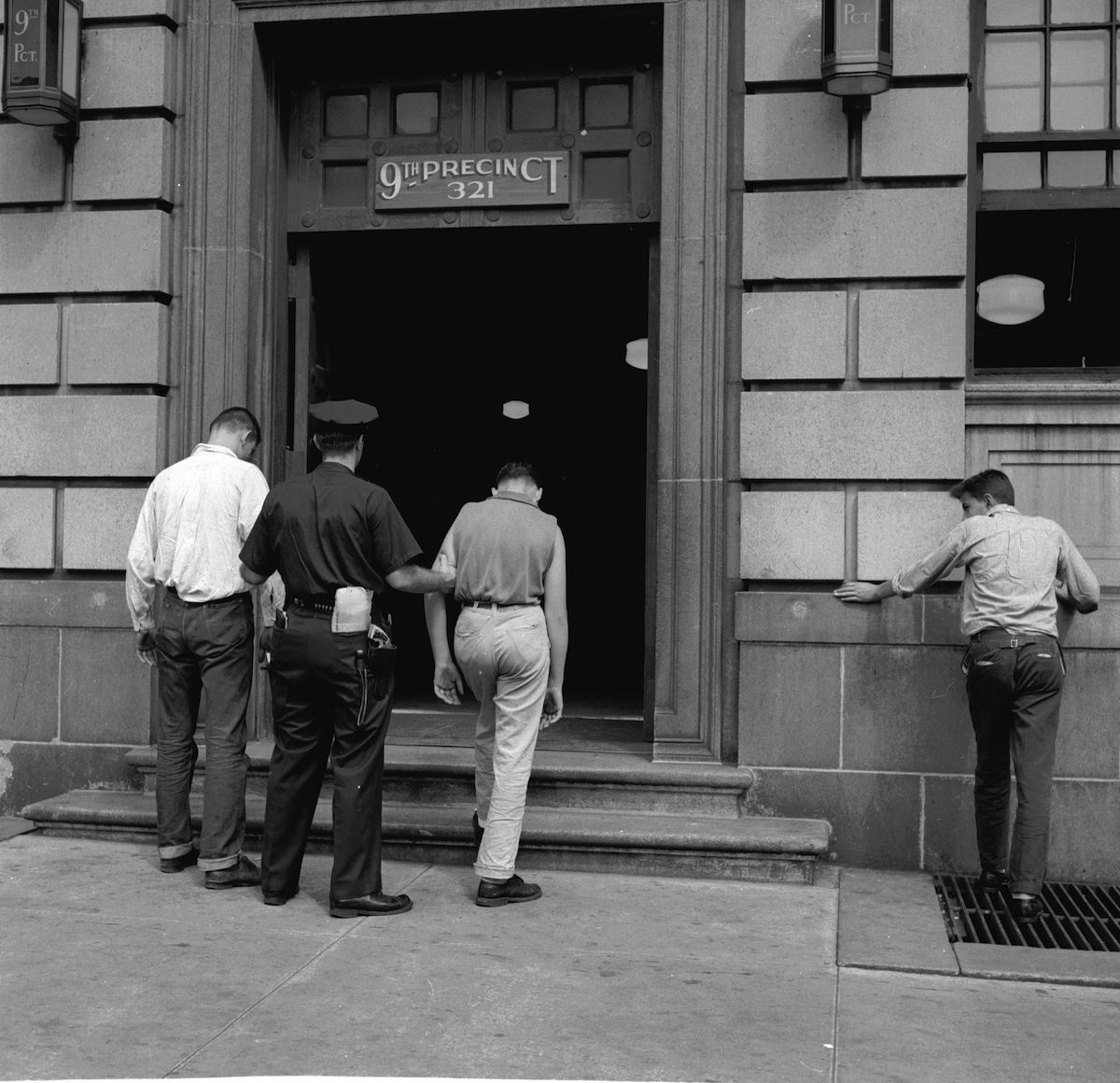 circa 1955:  Two members of a teenage street gang are taken into the 9th Precinct police station after their arrest in New York City.