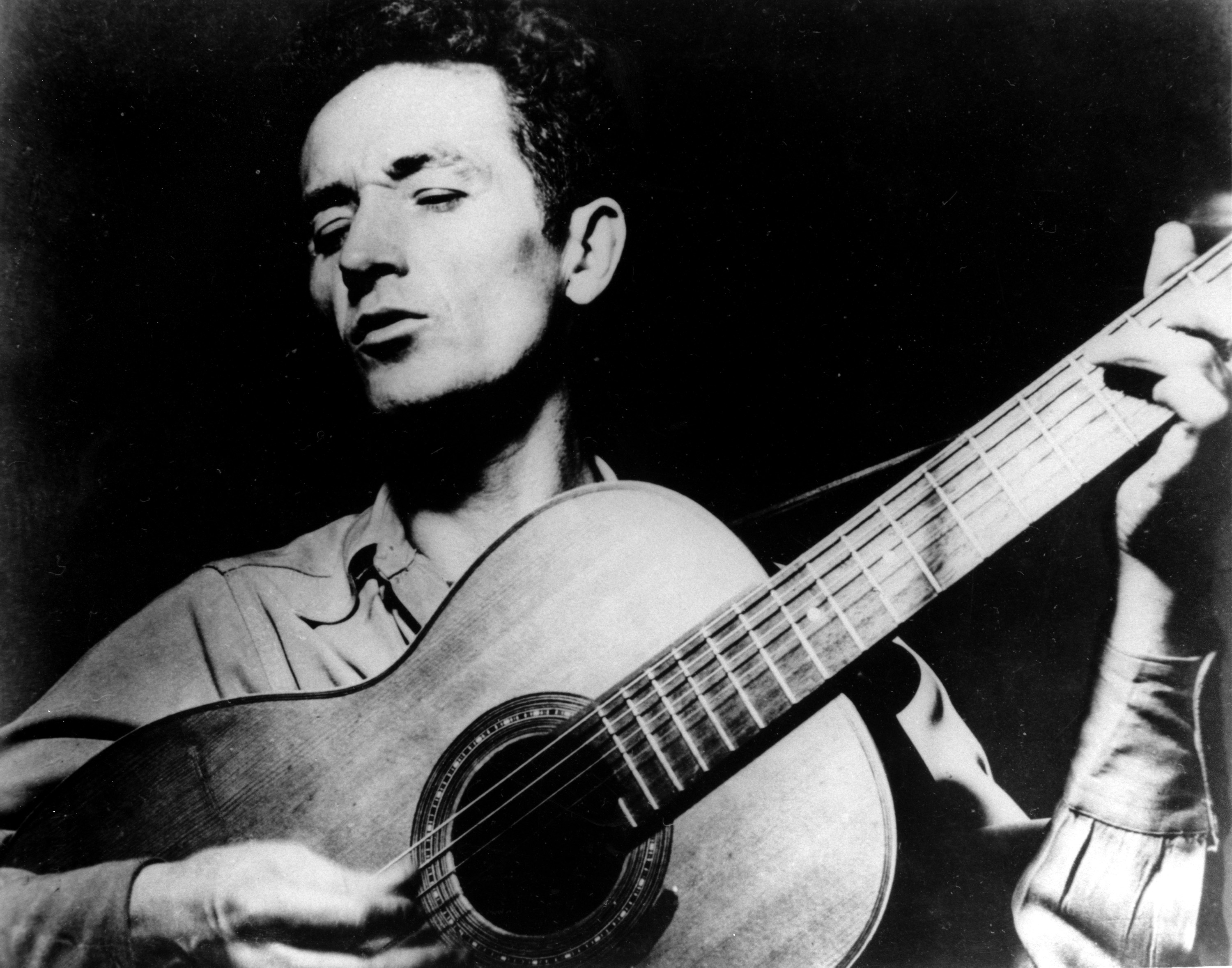 Folk singer, Woody Guthrie, singing a song and playing his guitar.
