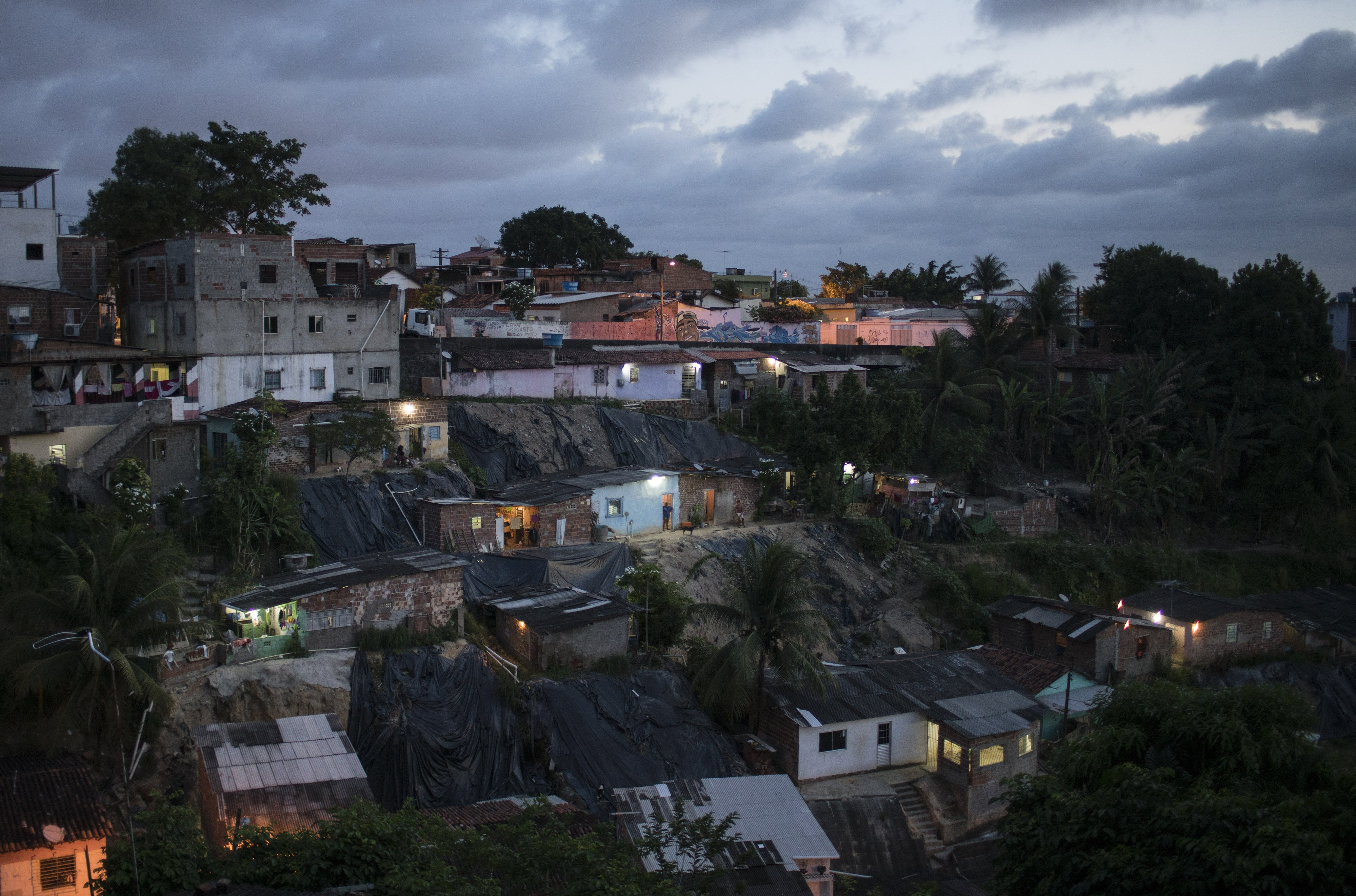 Homes are lit as the sun goes down in Ibura, one of the neighborhoods with the highest numbers of suspected cases of children born with microcephaly in Recife, Brazil, Jan. 27, 2016.