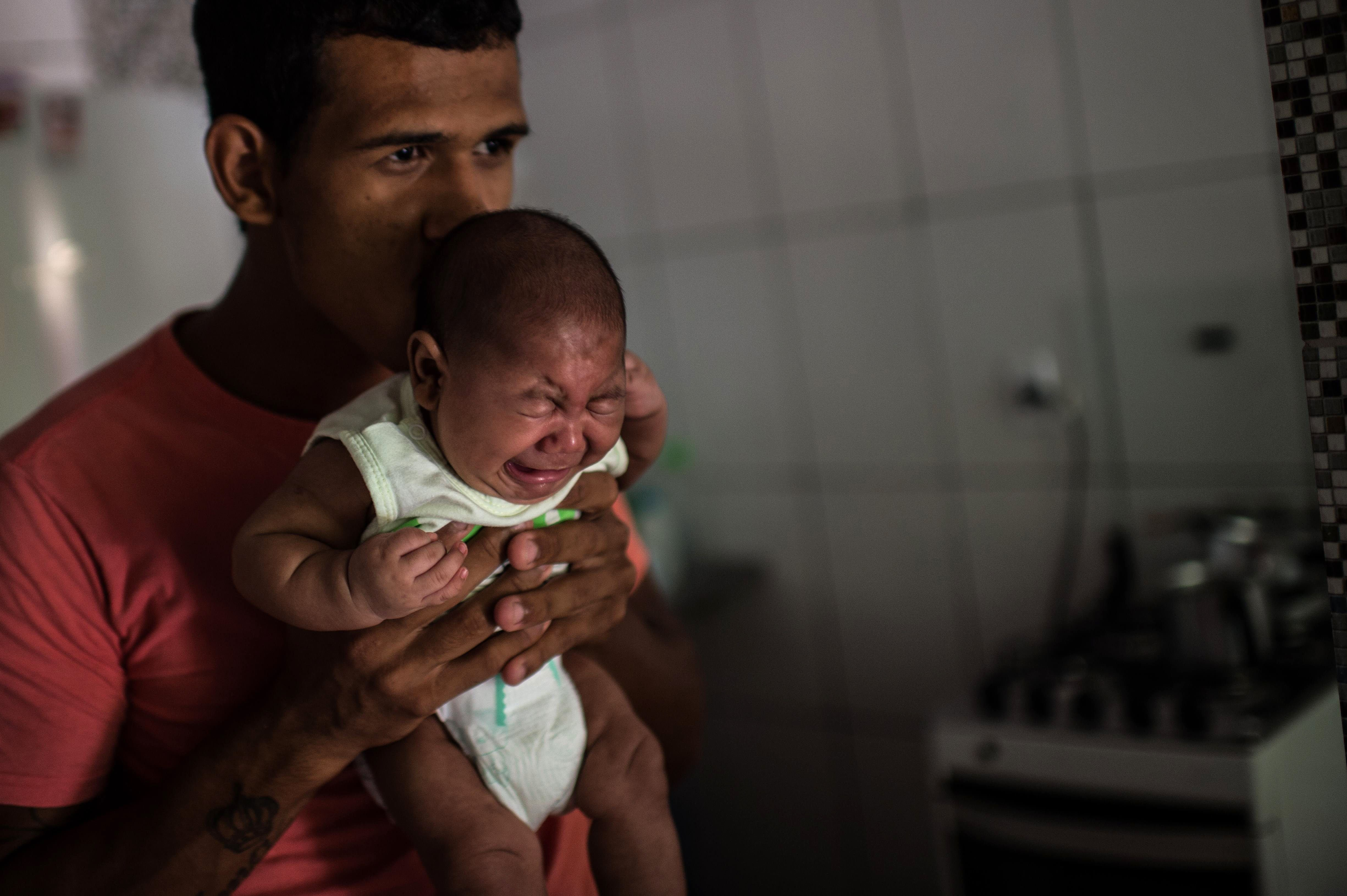 Matheus Lima, 22, holds his two-year-old son, Pietro, who suffers from microcephaly, at his home in Salvador, Brazil, Jan. 28 , 2016.