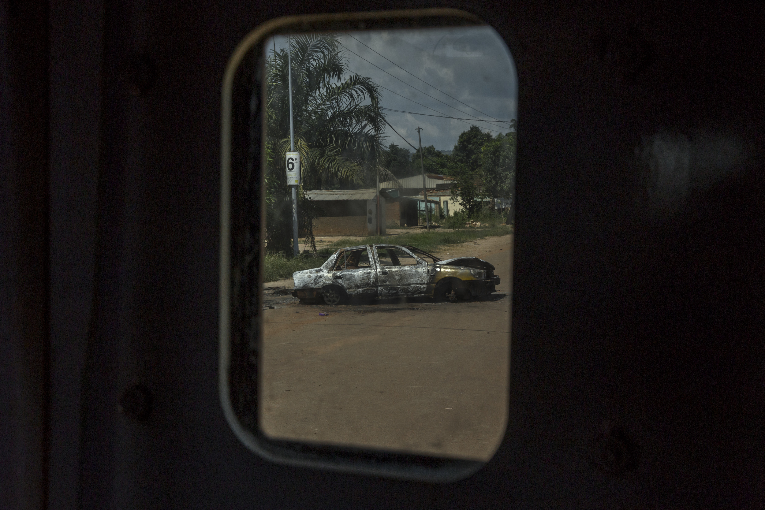 A burned car is seen from the window of a United Nations armored vehicle, a few days after heavy clashes erupted in Bangui following the murder of a young Muslim, on Oct. 3, 2015.