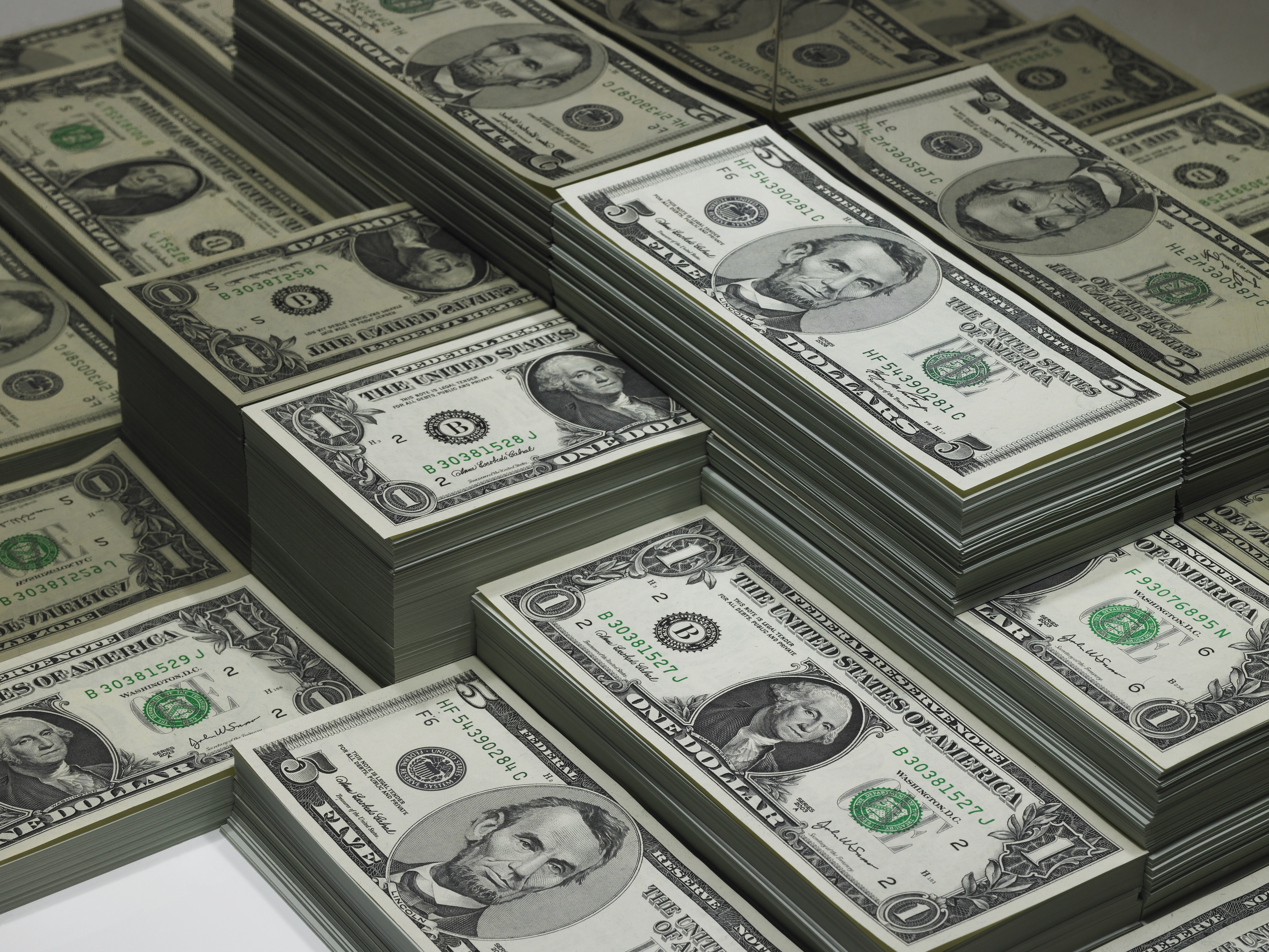 piles of dollar bills reflected in glass