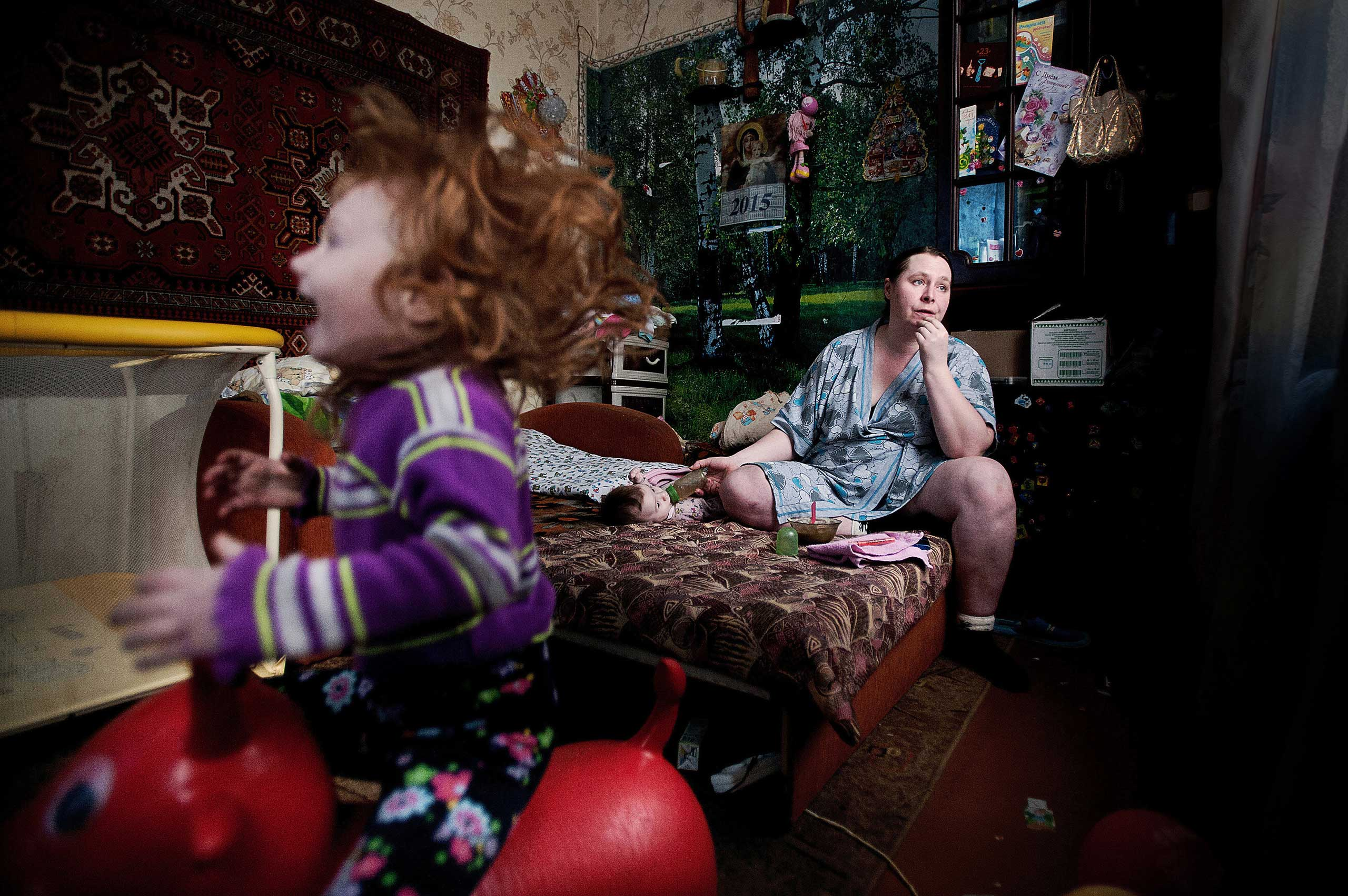 Local Solvichegodsk family, Oksana and her two kids, Sothia, who was born with heart disease. Over 50% of their salary is spent on utilities. They own this little room in the old house.