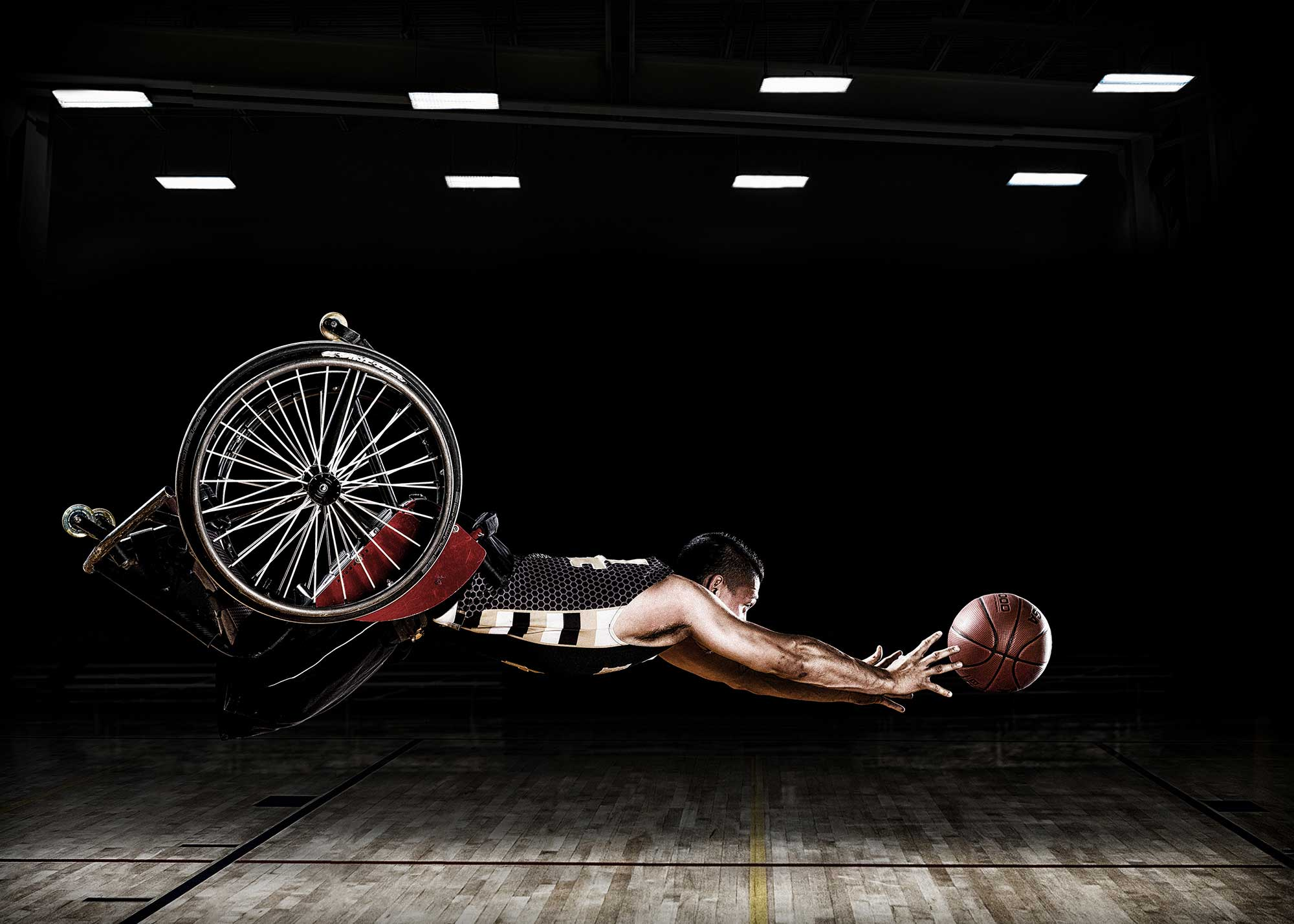 A RIC Hornets wheelchair basketball team member reaches for a basketball. These images were created for the Rehabilitation Institute of Chicago's Adaptive Sports Program.
