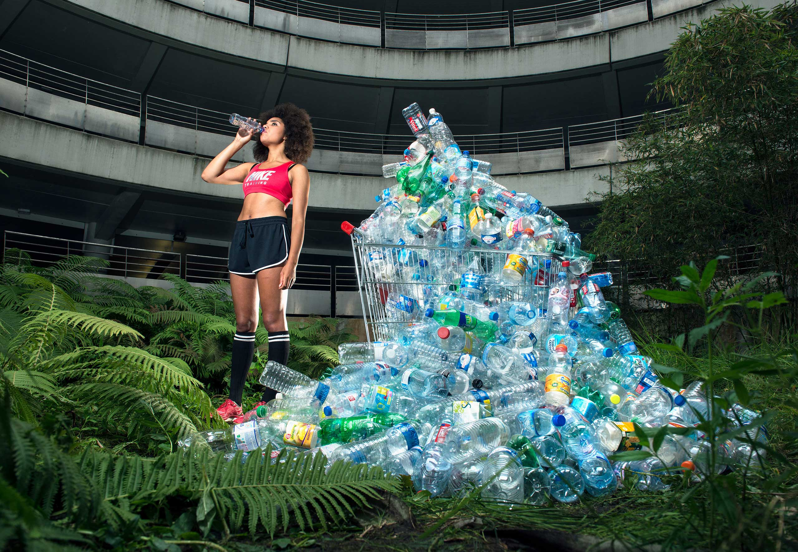 A woman drinks out of a water bottle near a  waste bank  of recycled waste in France. It's part of an exhibition exploring the excessive waste habits.