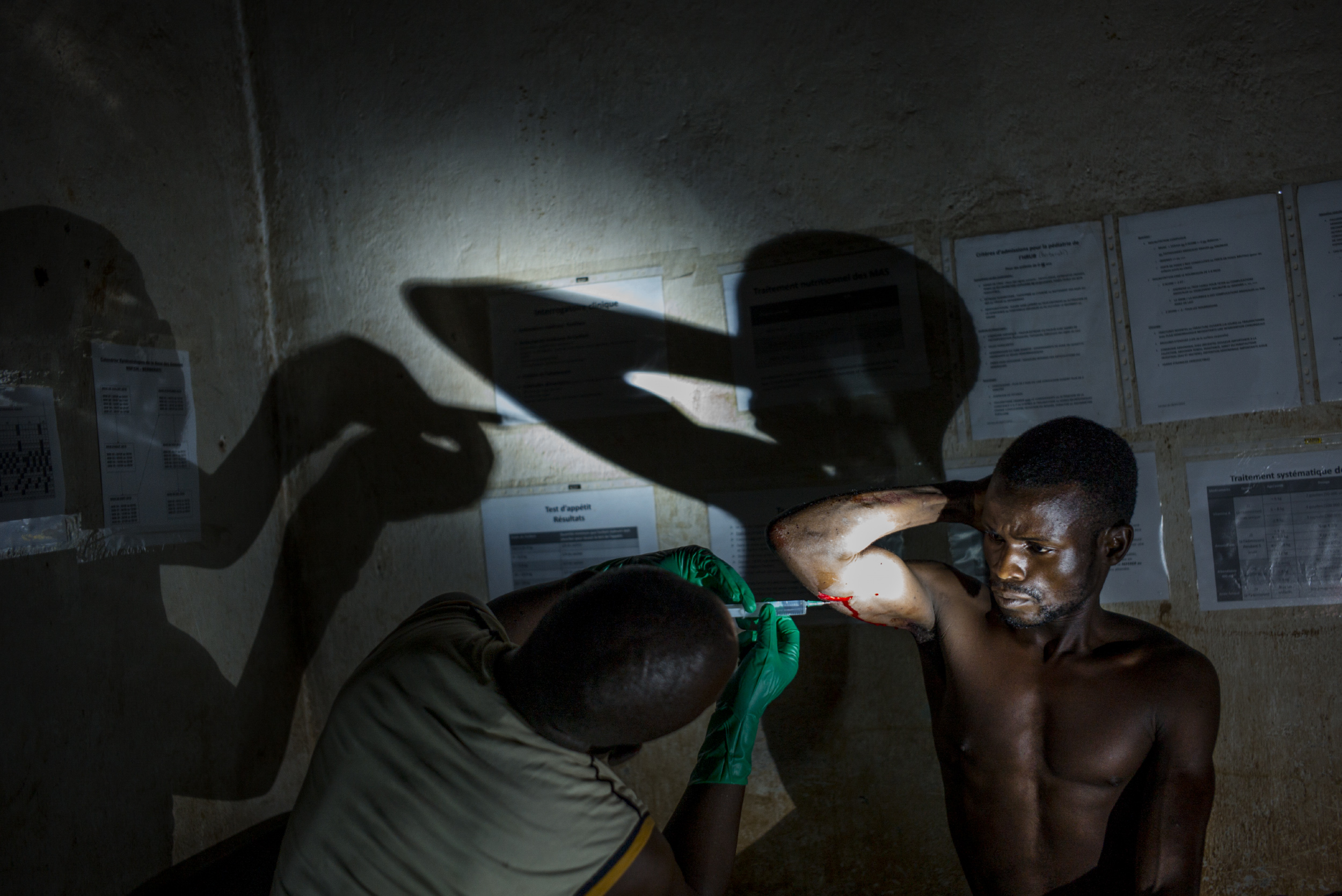 A man accused of sorcery is treated by a nurse from Doctors Without Borders at night without electricity in Amada Gaza, Central African Republic, Oct. 14, 2015.