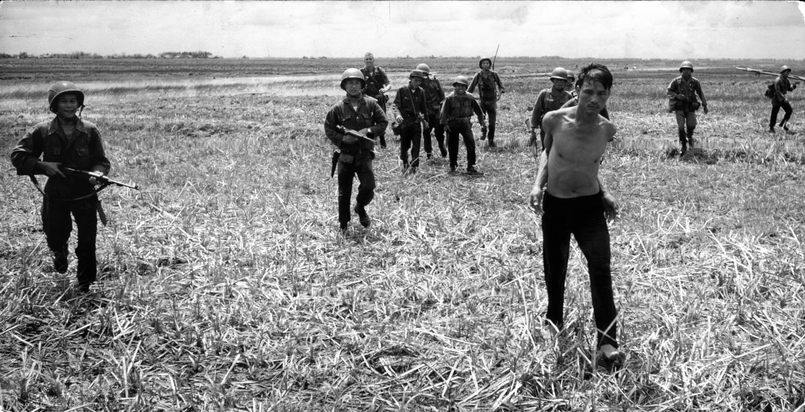 Vietnamese paratroopers escort a Vietcong suspect to a waiting helicopter after catching him with Communist propaganda, ca. 1961-1962.