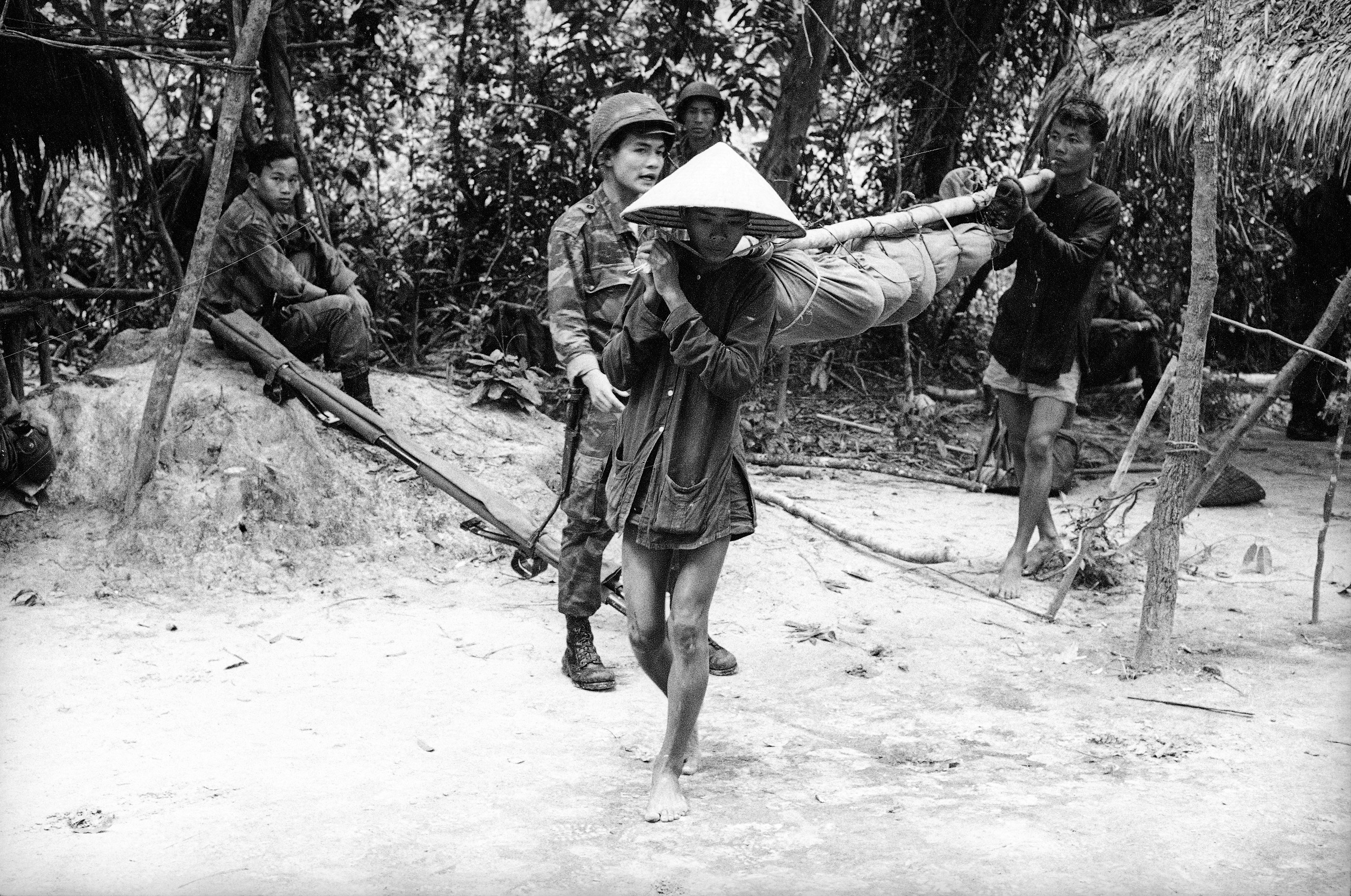 Villagers carry the body of fallen soldier, ca. 1961-62.