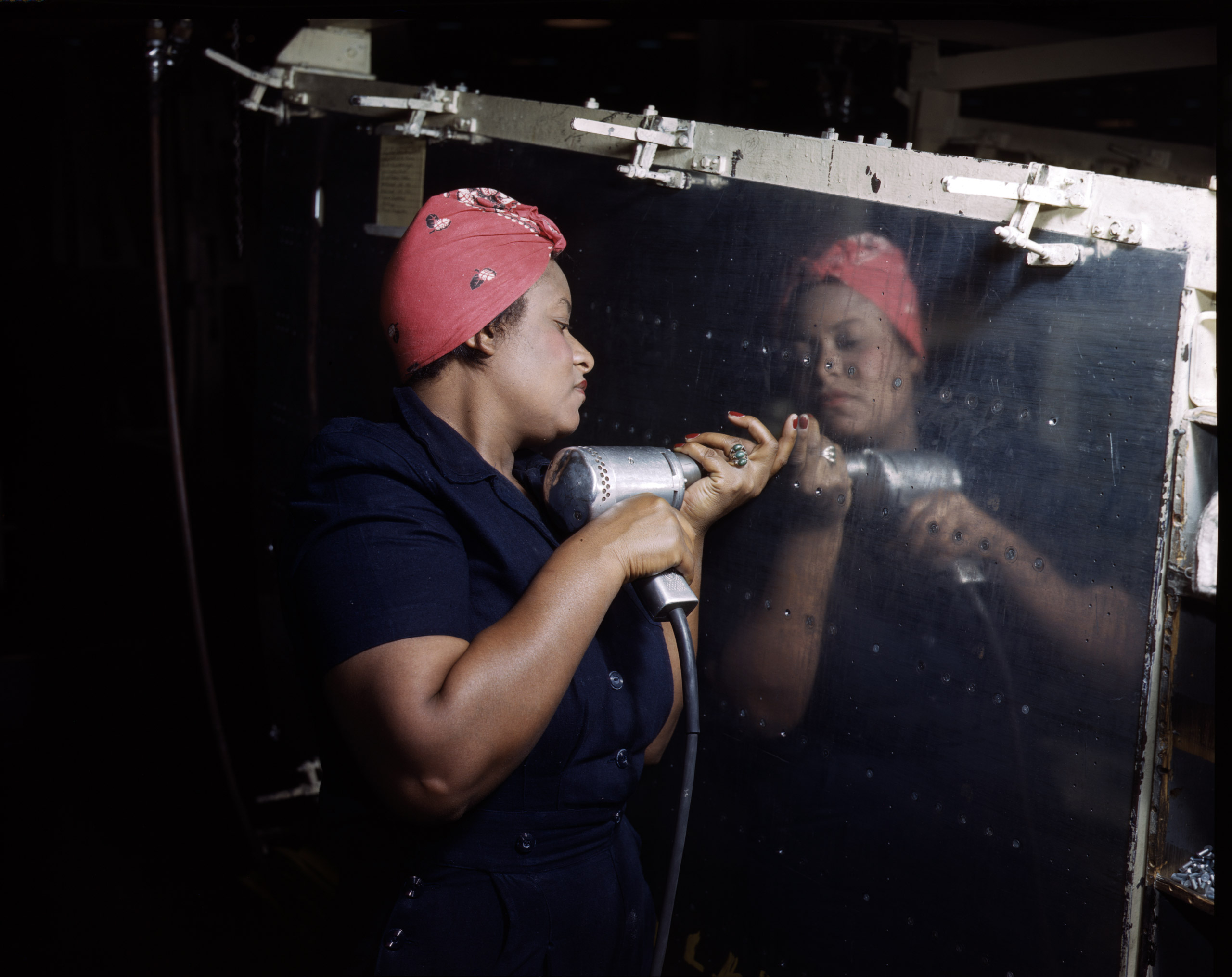 Operating a hand drill at Vultee-Nashville, woman is working on a  Vengeance  dive bomber, Tennessee, February 1943. Photographed by Alfred T. Palmer for the Farm Security Administration.