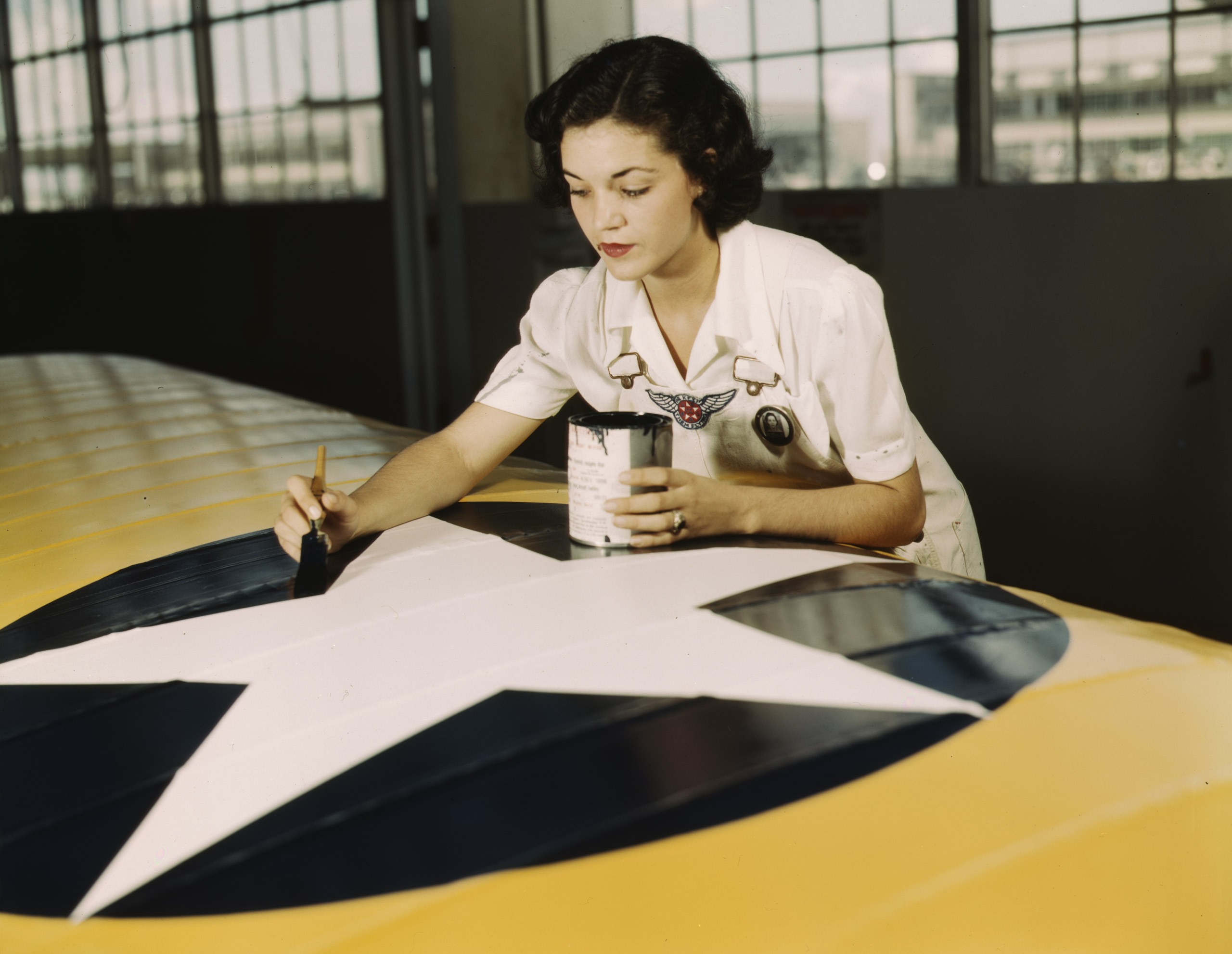Painting the American insignia on airplane wings is a job that Mrs. Irma Lee McElroy, a former office worker, does with precision and patriotic zeal. Mrs. McElroy is a civil service employee at the Naval Air Base, Corpus Christi, Tex. Her husband is a flight instructor. August 1942. Photographed by Howard R. Hollem for the Farm Security Administration.