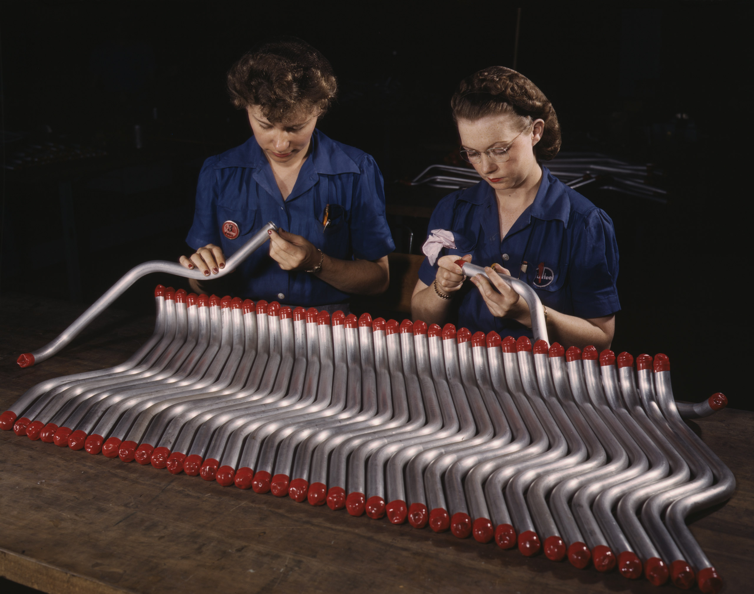 Two women workers are shown capping and inspecting tubing which goes into the manufacture of the  Vengeance  (A-31) dive bomber made at Vultee's Nashville division, Tennessee, February 1943. Photographed by Alfred T. Palmer for the Farm Security Administration.