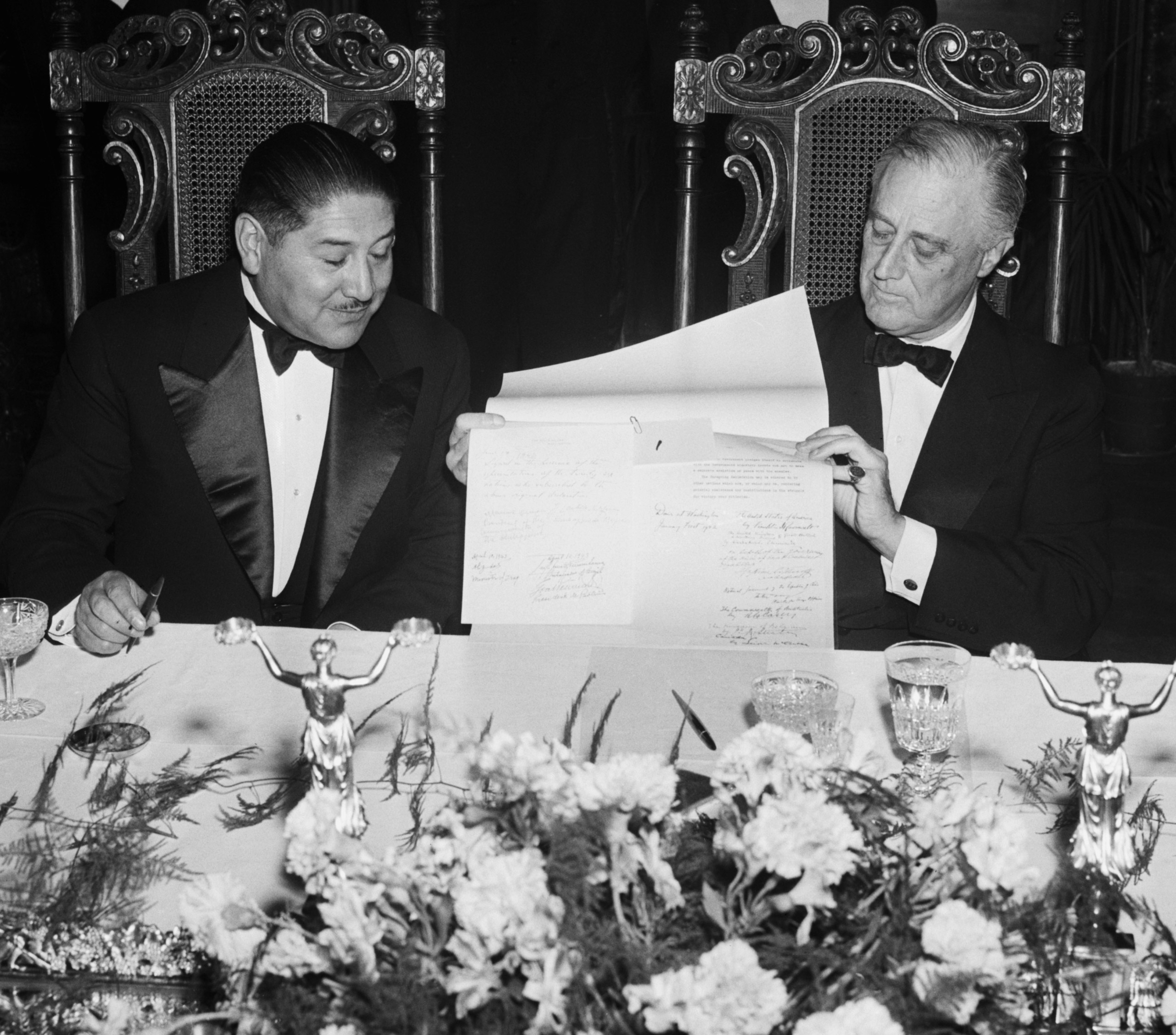 President Enrique Penaranda of Bolivia, and President Franklin Roosevelt of the United States at a White House state dinner on May 5, 1943. They are shown looking at the United Nations' pact, in which Penaranda pledged his country's tin-producing resources against the axis.