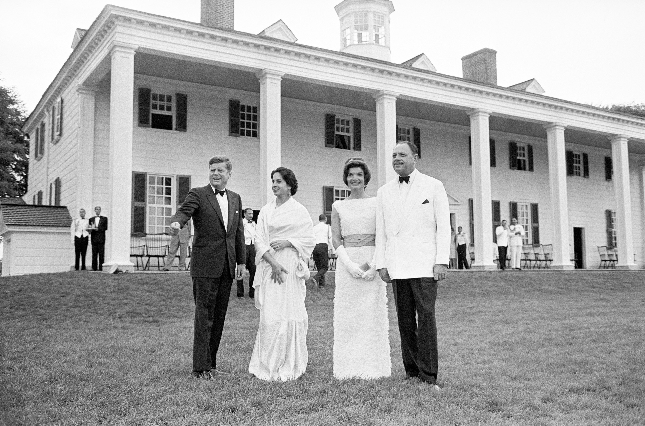 President Kennedy points out landmarks to Pakistan President Mohammed Ayeb Khan and his daughter, Begum Nasir Akhtar Aurangzeb, as they and Mrs. Kennedy pose near the home of George Washington tonight. The Kennedy couple entertained their Pakistani guests at a state dinner on the lawn of historic Mt. Vernon. July 11, 1961.