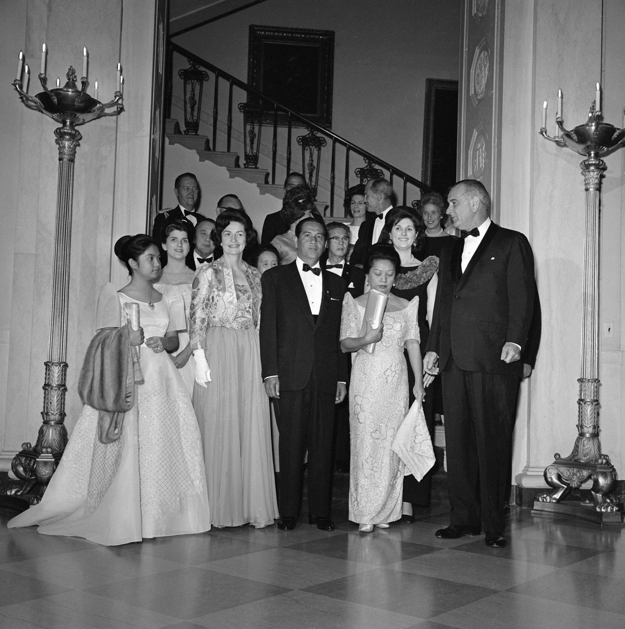 President and Mrs. Johnson entertained guests at a State Dinner in honor of Philippines President and Mrs. Diosdado Macapagal in 1964. Shown here just prior to the dinner are left to right- Gloria Macapagal, daughter of the President; Mrs.Johnson; Philippine Ambassador Oscar Ledesma (partly hidden behind Mrs.Johnson); California Governor Edmund Brown (glasses, behind the Ambassador); Mrs.Ledesma; President Macapagal; Lynda Johnson, daughter of the President; President Johnson; and Secretary of State Dean Rusk (partly hidden behind President Johnson).