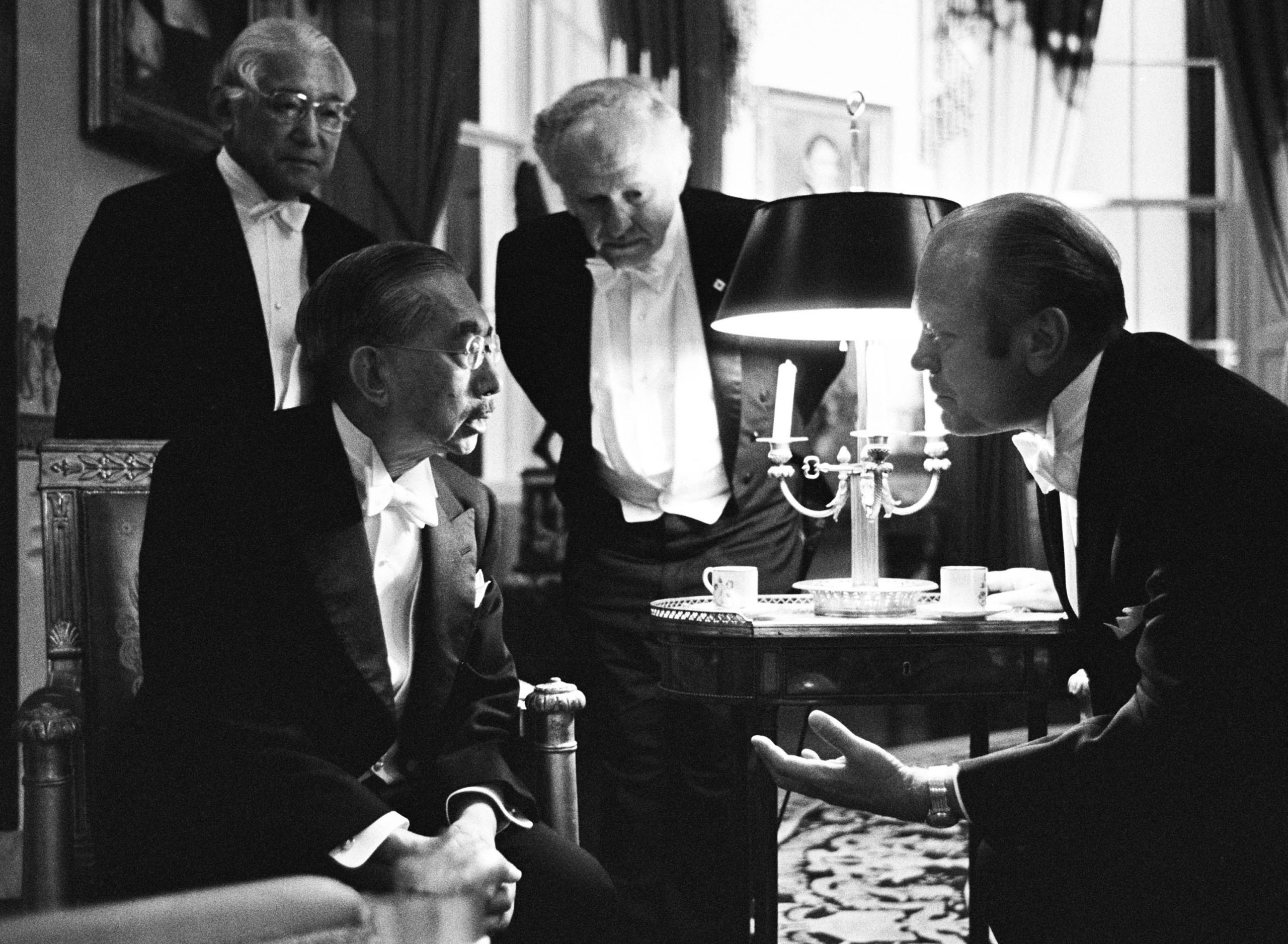 With their interpreters to aid them, Emperor Hirohito of Japan and President Gerald R. Ford chat in the Blue Room on the occasion of the state dinner in honor of the Emperor and Empress Nagako on Oct. 2, 1975, at the White House in Washington, D.C.