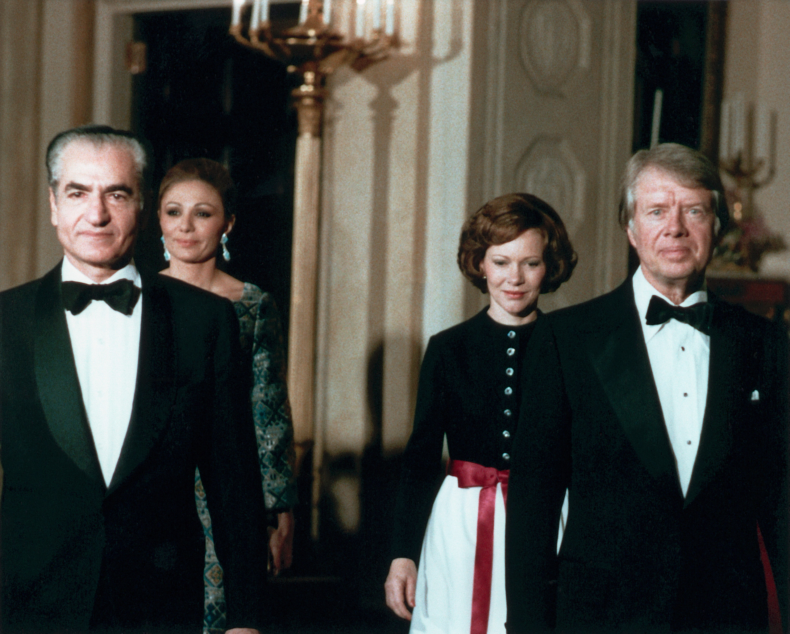 President Carter and wife Rosalynn escort the Shah and Shahbanou of Iran to a state dinner in the White House, 1977.