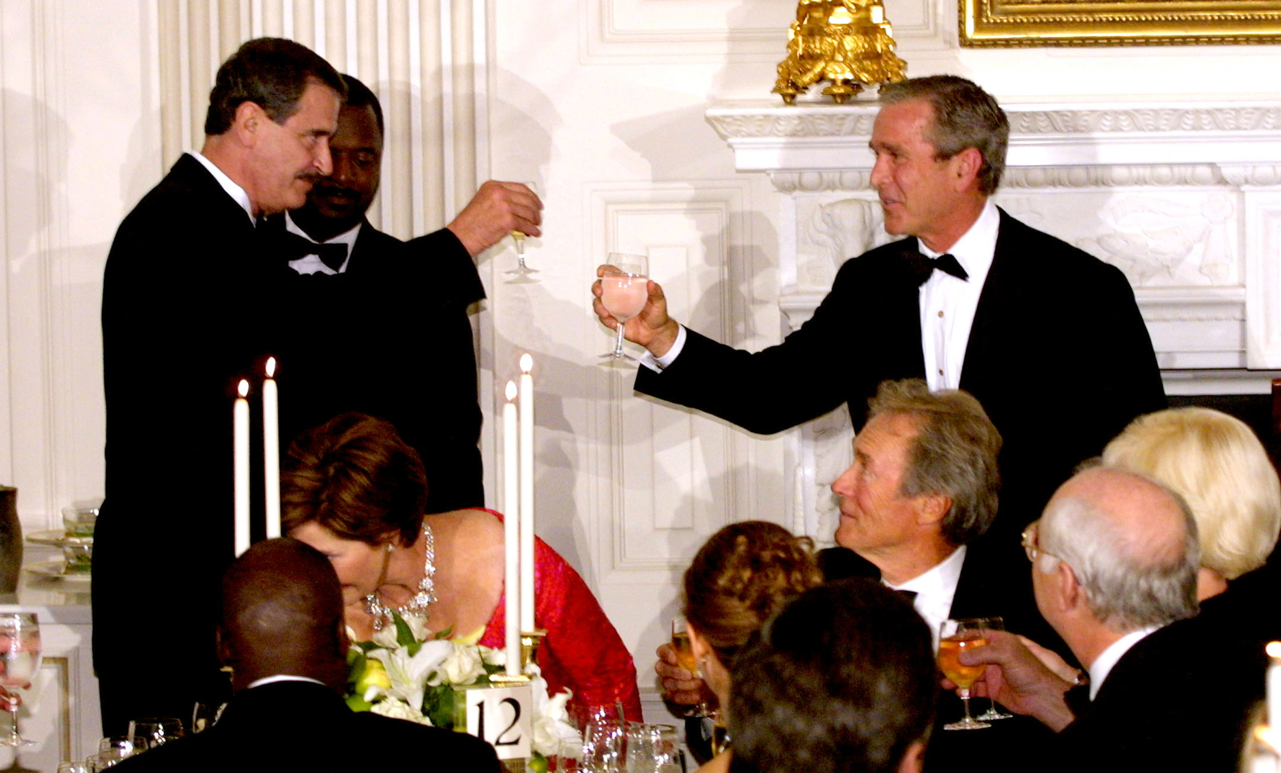 President George W. Bush and Mexican President Vicente Fox raise their glasses in a toast Sept. 5, 2001 at a state dinner for Fox at the White House in Washington, DC. Actor Clint Eastwood is seated at the right.