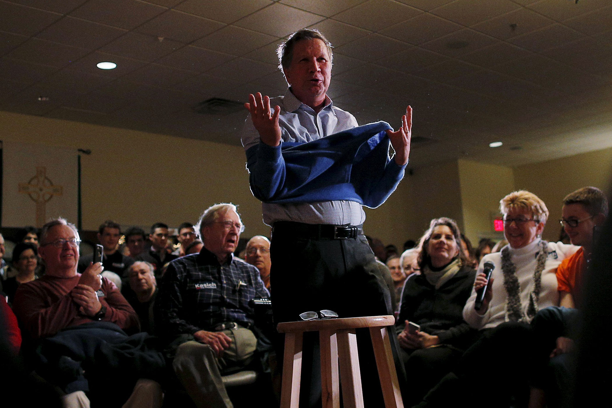 Republican presidential candidate Ohio Gov. John Kasich takes off his sweater during a campaign town hall meeting in Worcester, Mass. on Feb. 20, 2016.
