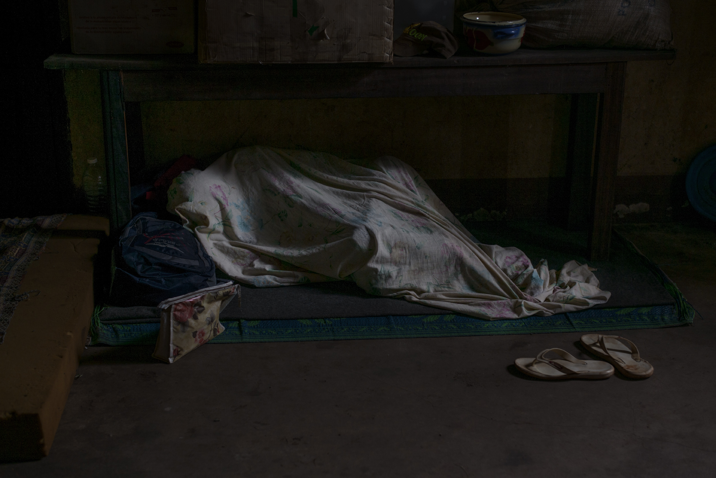 A Muslim man sleeps under a sheet at a church in Carnot, where he is taking refuge with other Muslims following violence by antibalaka, Oct. 21, 2015.