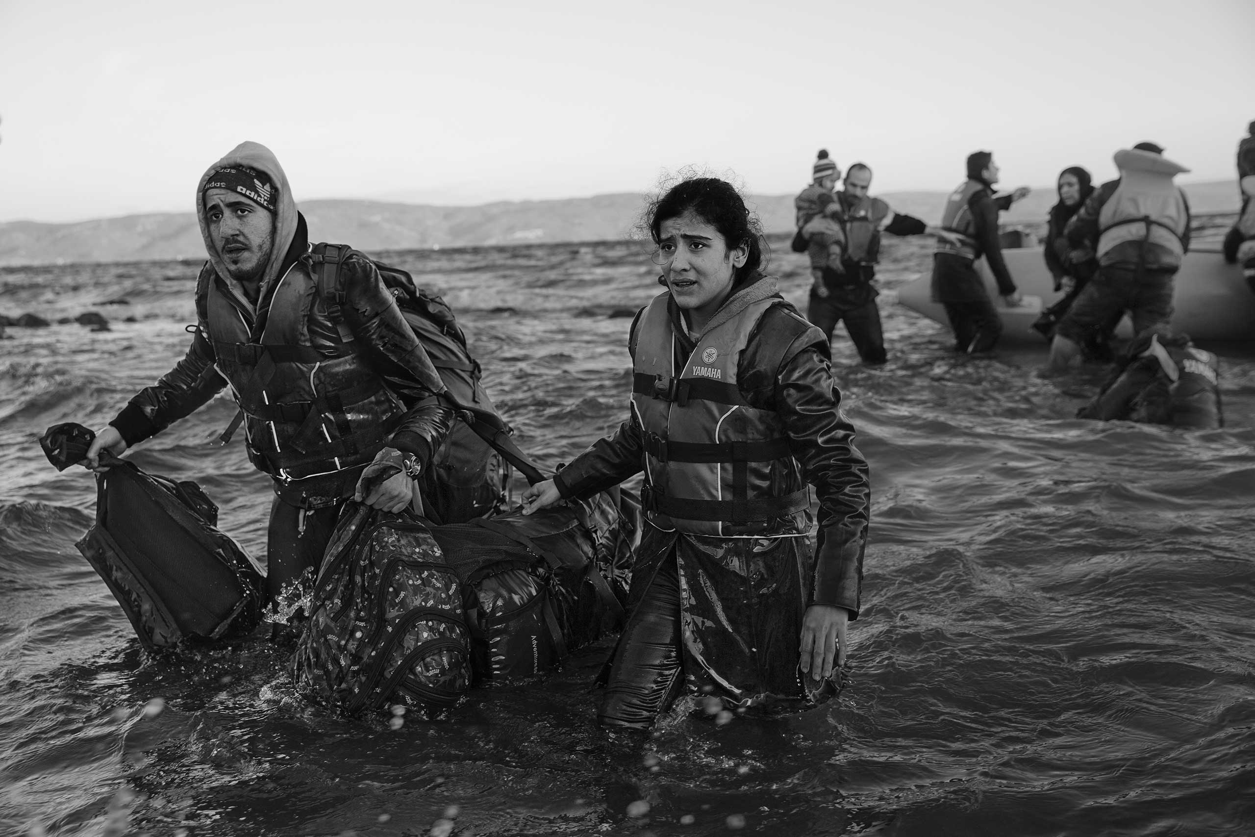 A man and woman carry their belongings to Lesbos after their inflatable boat became stuck on the rocks about 160 feet from the Greek shore.