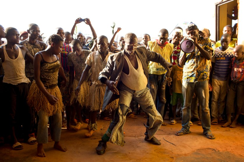 A man disguised as pregnant woman dances to welcome candidate Anicet Georges Dologuelé, who is running for president, at the aerodome in Mobaye, Central African Republic, Dec. 20, 2015.