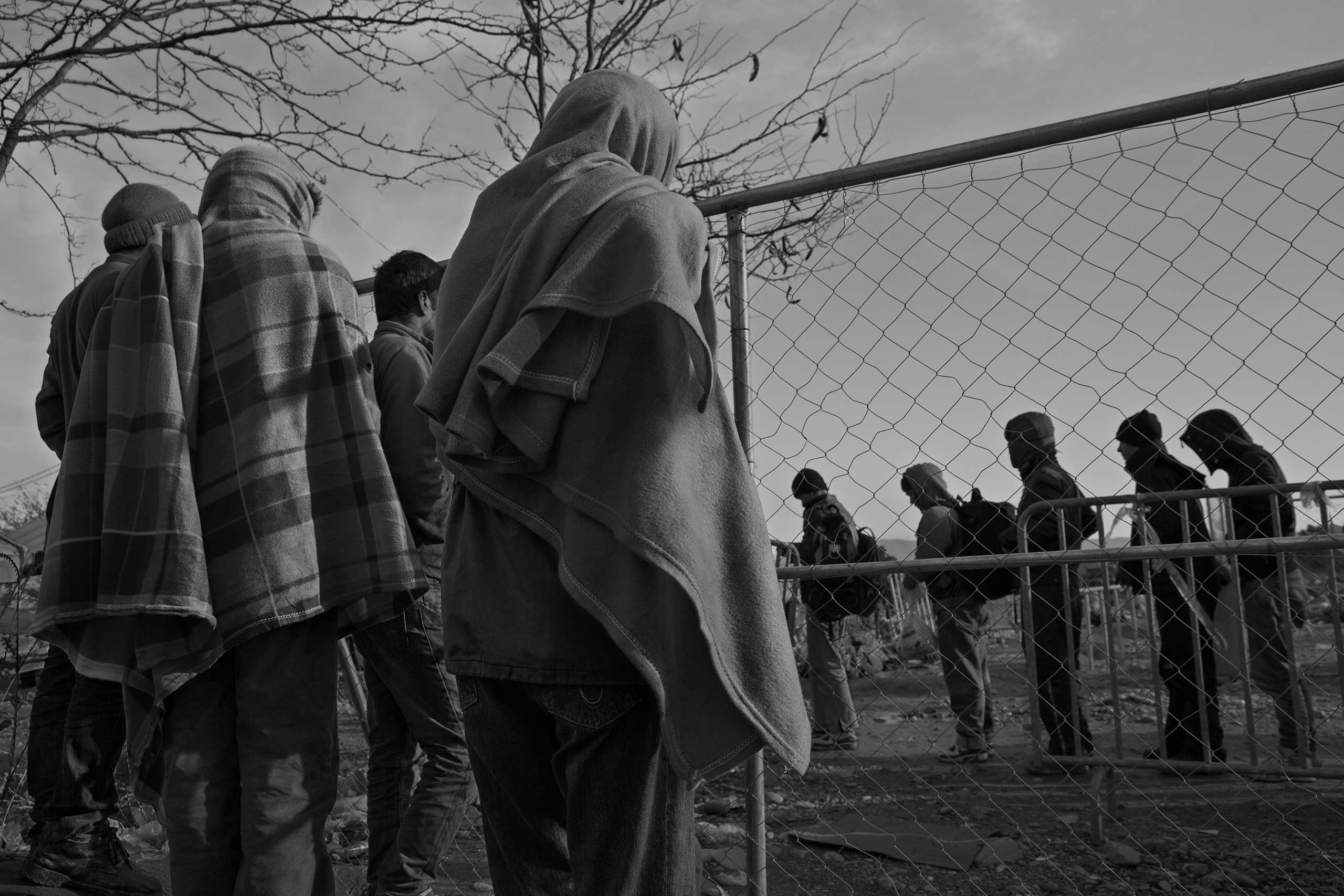 Refugees and migrants from Morocco, Iran, Pakistan, Bangladesh and Somalia, who are not permitted to cross from Greece into Macedonia, watch as those from war-torn countries of Afghanistan, Iraq and Syria, pass into Macedonia.
