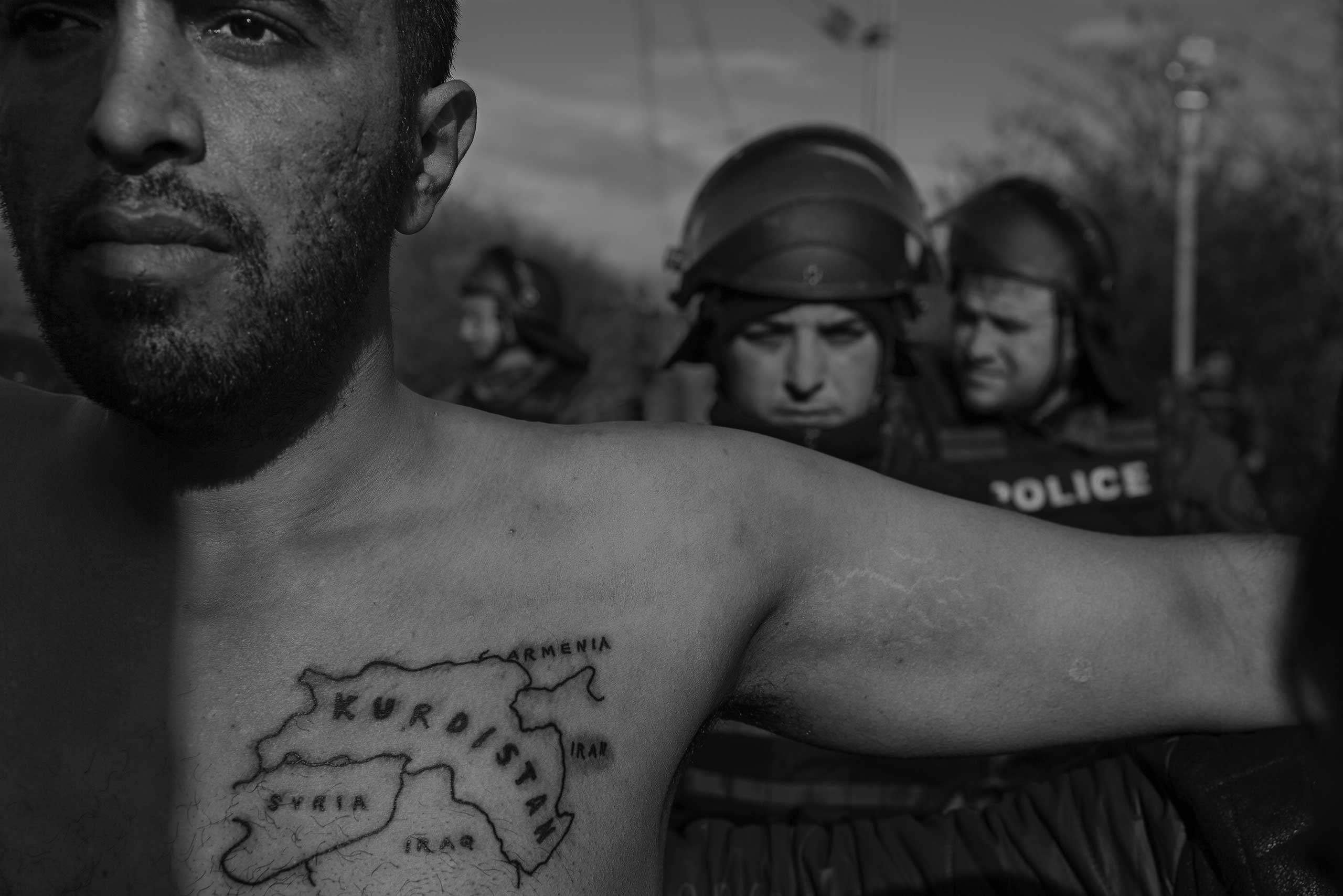 A man spreads his arms in a bid to defuse tensions between asylum seekers and police at a demonstration at the Macedonian border.