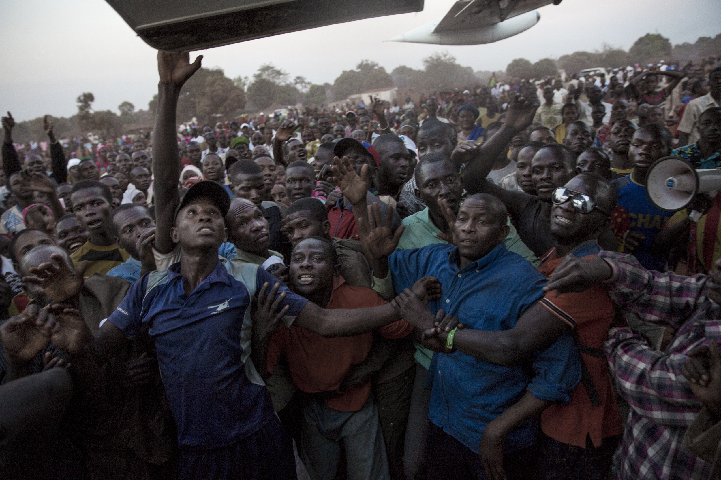 Supporters of Muslim presidential candidate Karim Meckassoua are held back at an airport in Bria, eastern Central African Republic, Dec. 24, 2015. Thousands of supporters, some asking for money, came to welcome him.