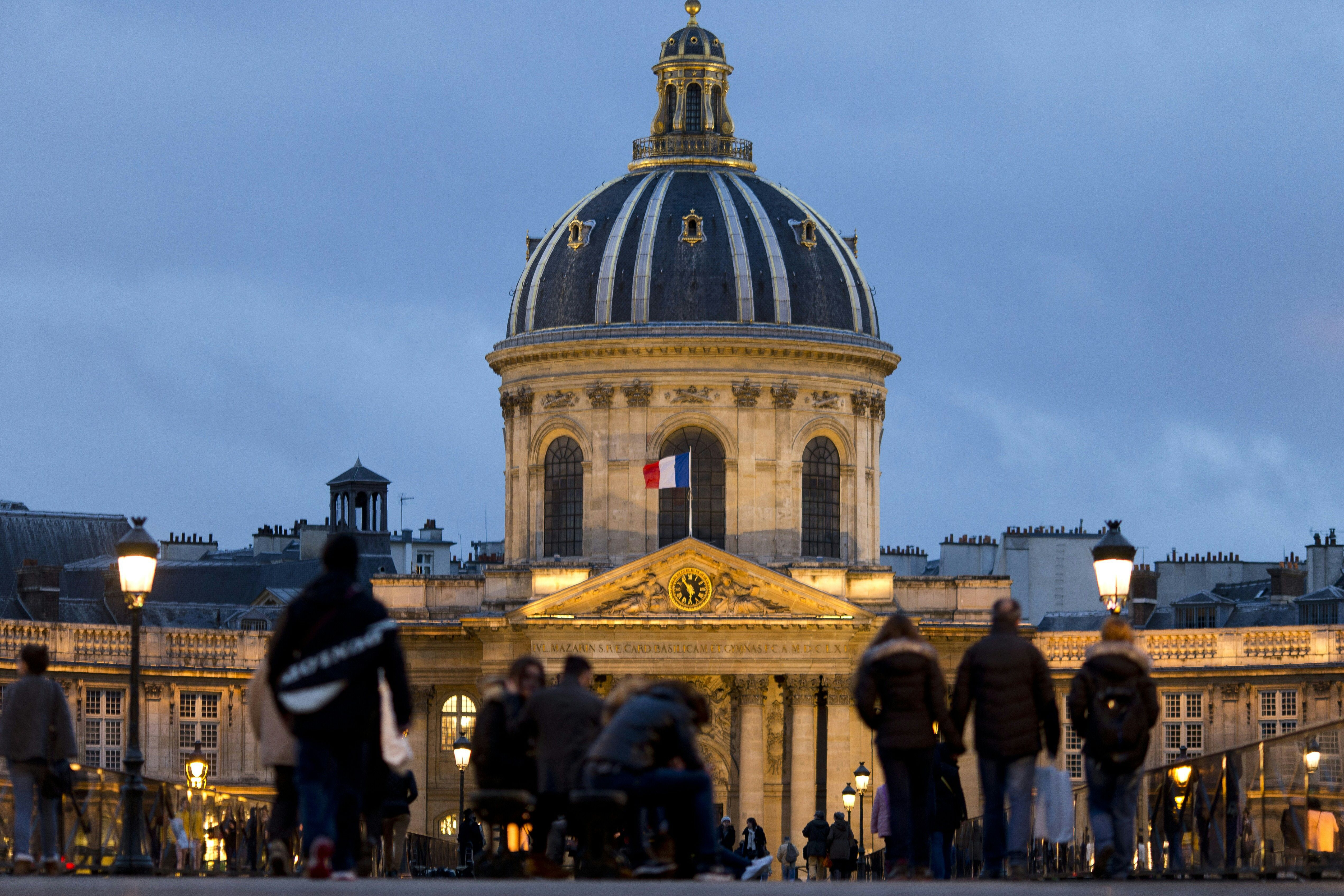 People walk on a bridge in front of the Institut de France building which houses the Academie Francaise in Paris on Feb. 1.