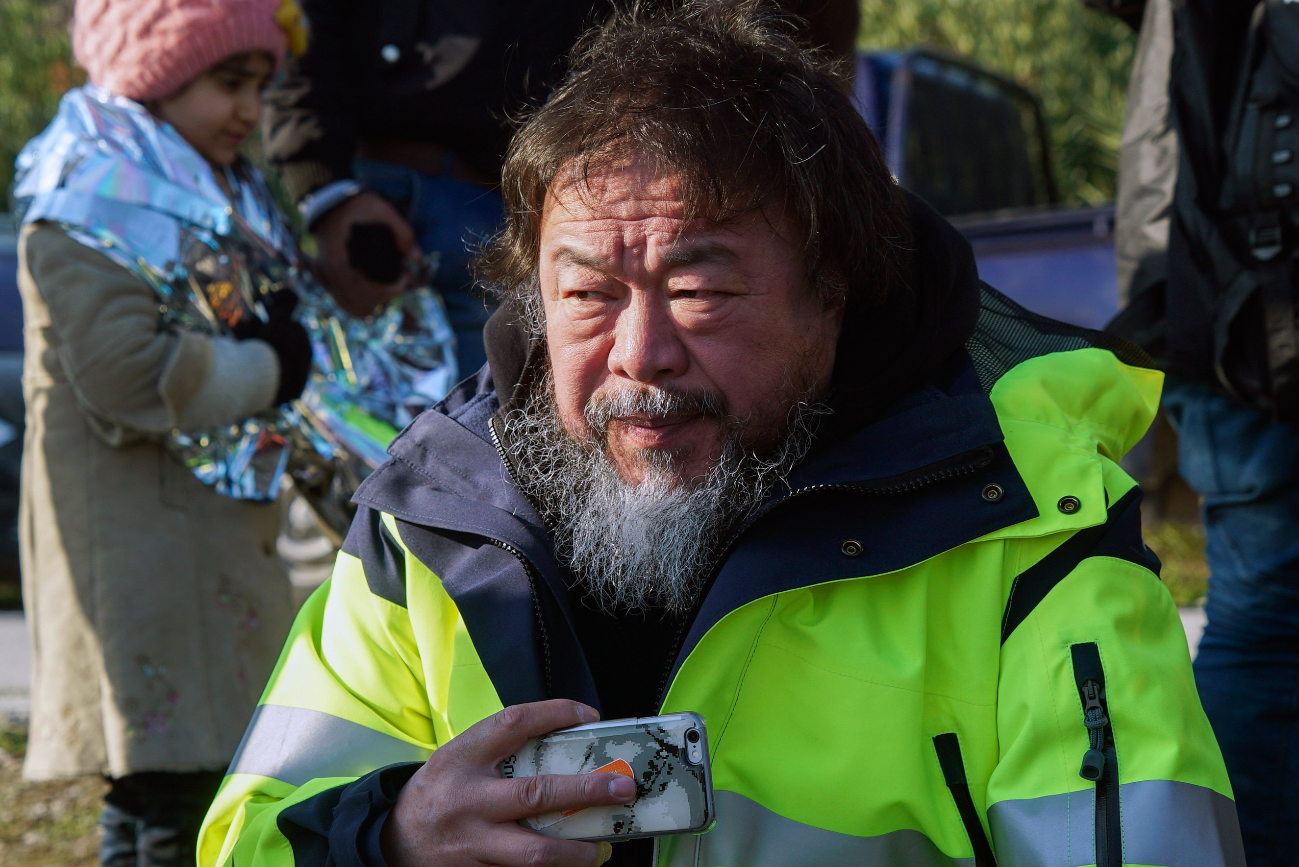 Chinese activist and artist Ai Weiwei assists refugees and migrants after their arrival from the Turkish coast to a beach on the Greek island of Lesbos, Jan. 28, 2016.