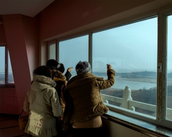 South Korean tourists point in Hunchun, China, point toward North Korea across the Tumen River. The Russian border lies to their left.