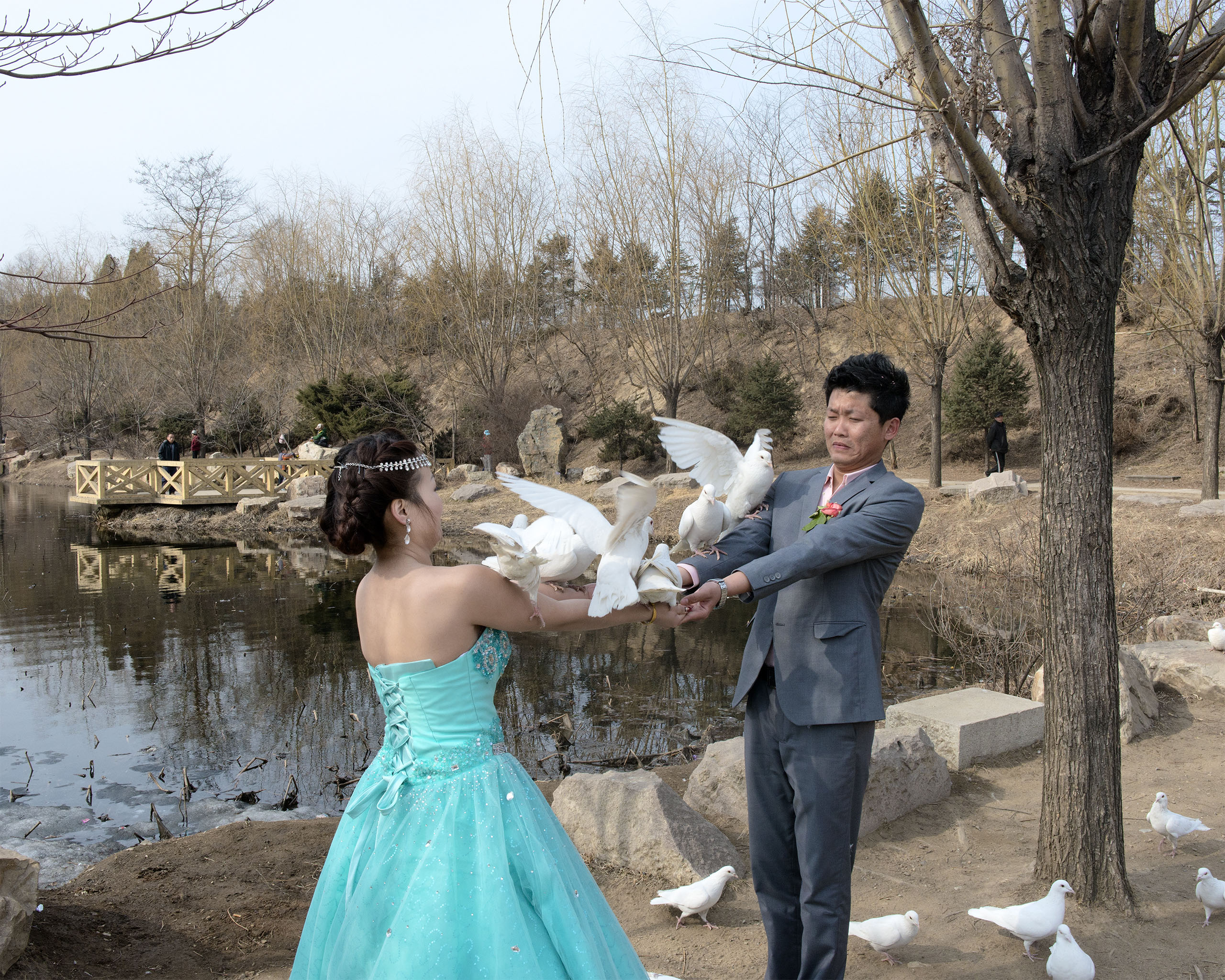 A newly married couple poses with white pigeons for a photo shoot in Dandong, China.  Dandong is situated on the banks of the Yalu River, a short distance from North Korea.