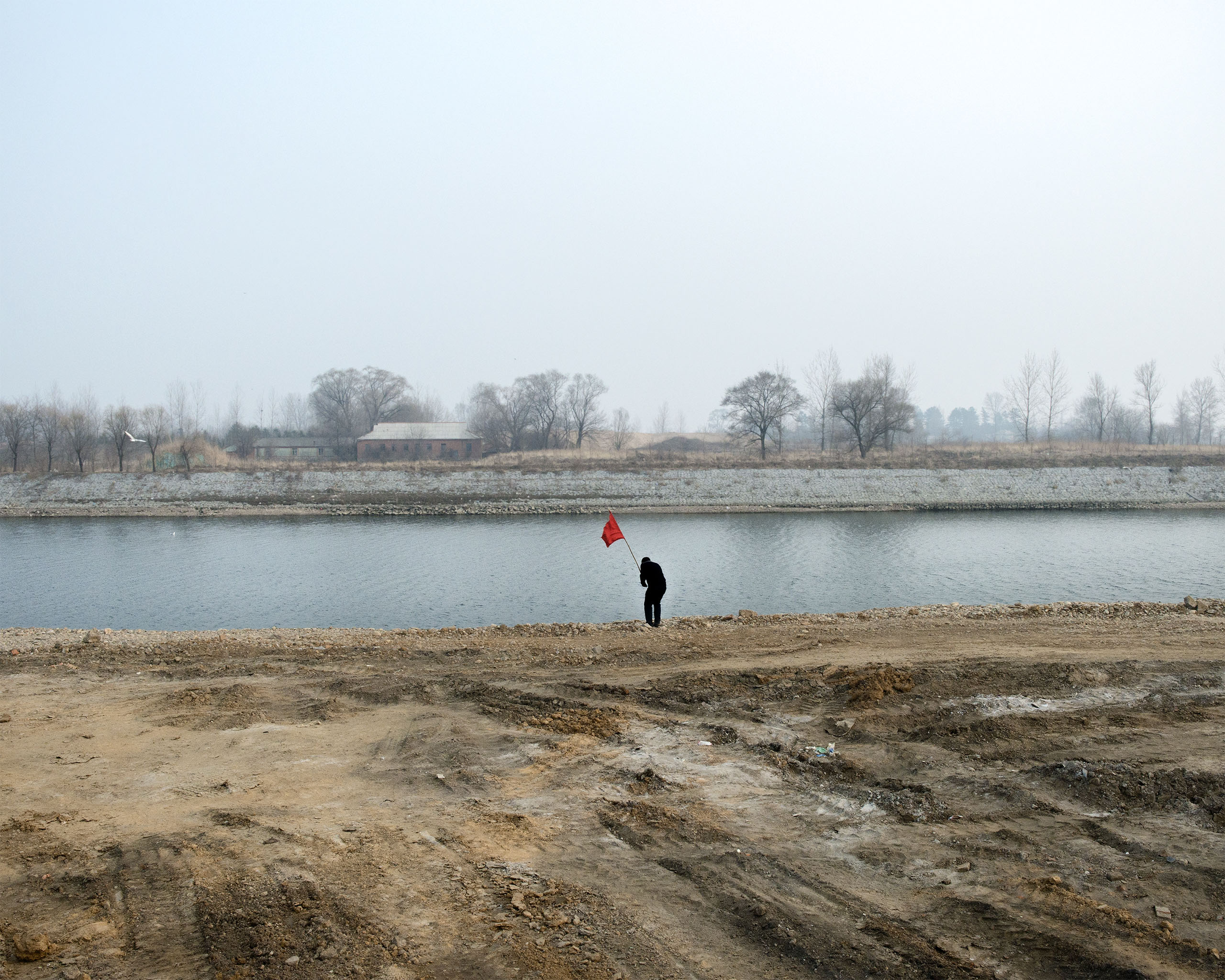 A man places a red flag at the river bank across from north korea border in  Dandong, China.