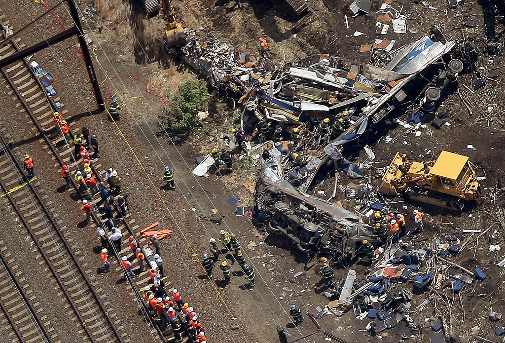Investigators and first responders work near the wreckage of an Amtrak passenger train carrying more than 200 passengers from Washington, DC to New York that derailed May 13, 2015 in north Philadelphia, Pennsylvania.