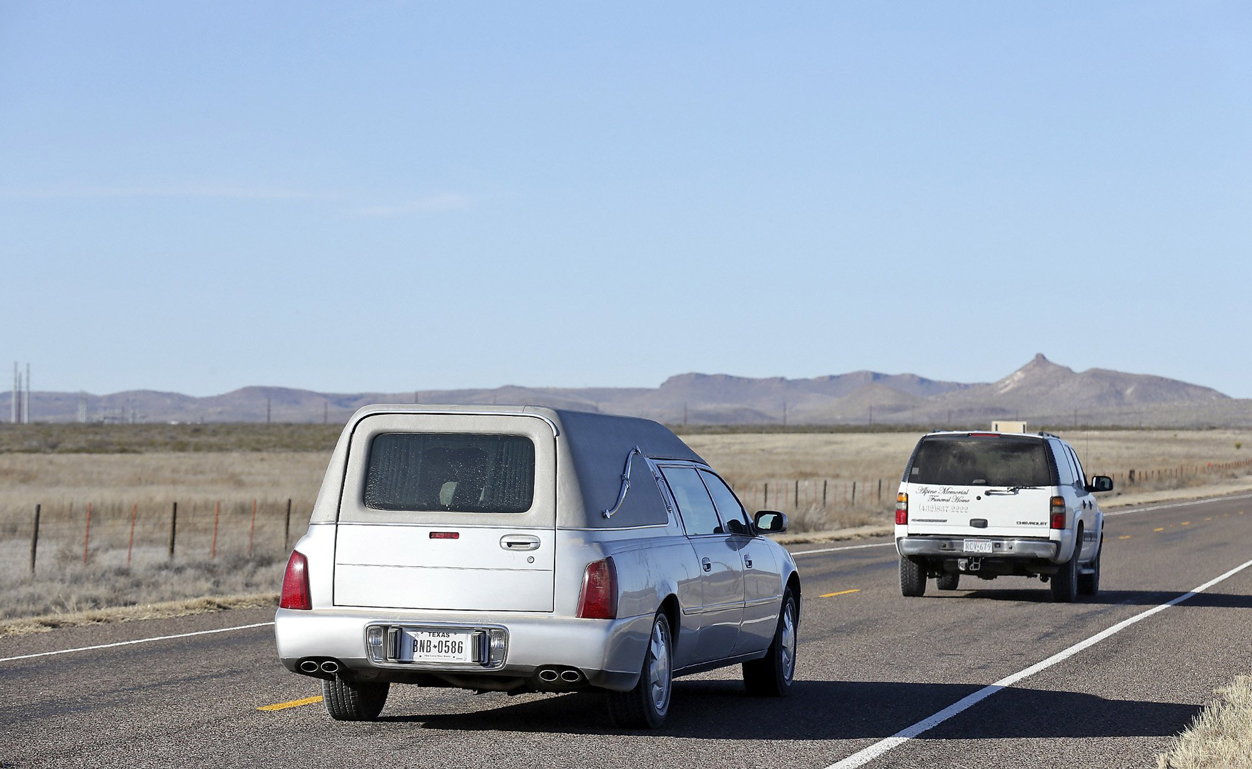 An SUV and hearse from Alpine Memorial Funeral Home transporting the body of late Supreme Court Justice Antonin Scalia leave Cibolo Creek Ranch in Shafter, Texas, on Feb. 13, 2016.