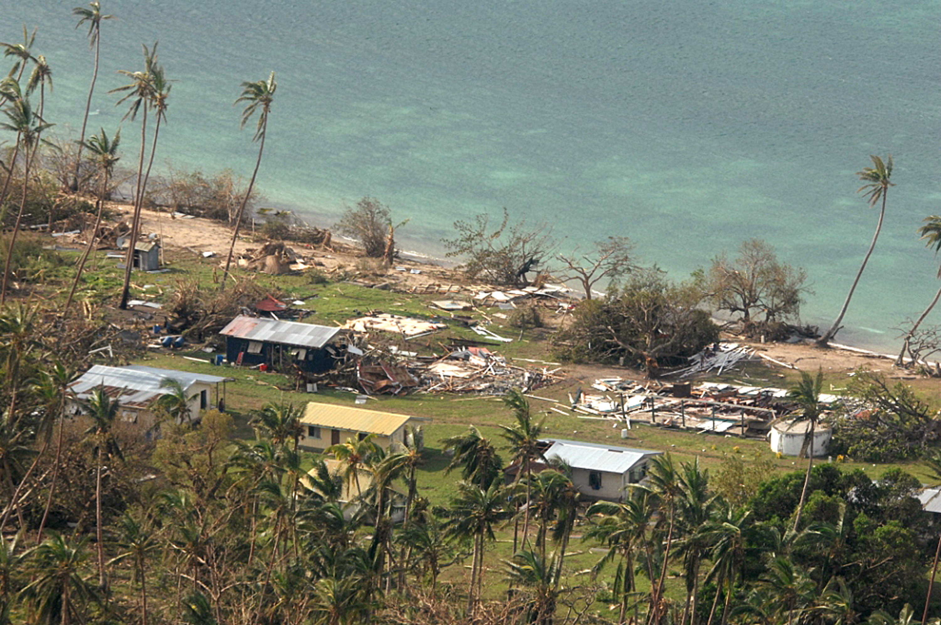 In this Sunday, Feb. 21, 2016 aerial photo supplied by the New Zealand Defense Force, debris is scattered around damaged buildings at Susui village in Fiji, after Cyclone Winston tore through the island nation.