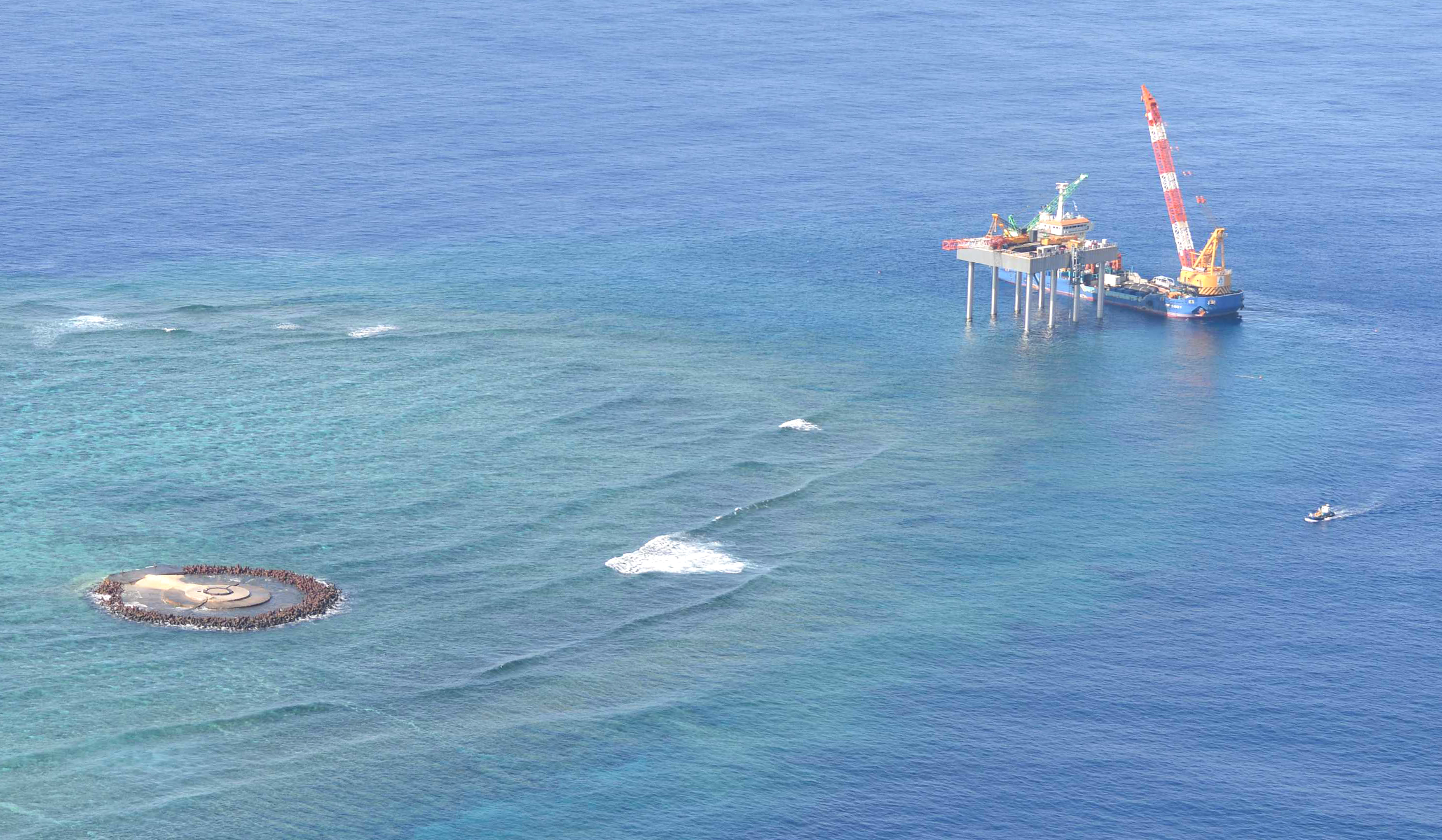A photo from Yomiuri's jet airplane shows a boat towing a barge  near Okinotorishima island, Japan's southernmost island