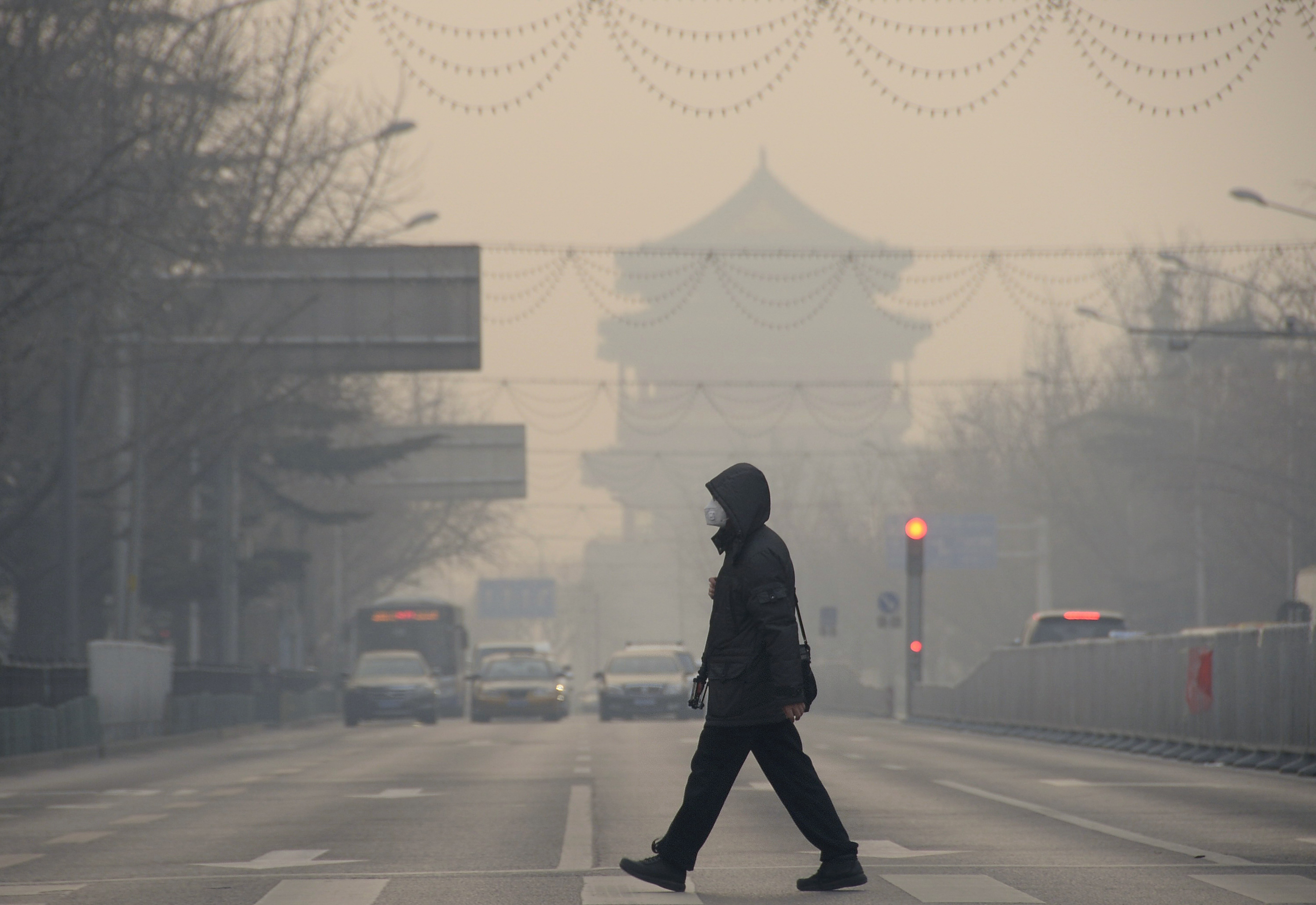 A pedestrian walks amid heavy smog in Beijing, capital of China, Dec. 29, 2015. A blue alert for heavy air pollution was issued by Beijing municipal emergency response headquarters.