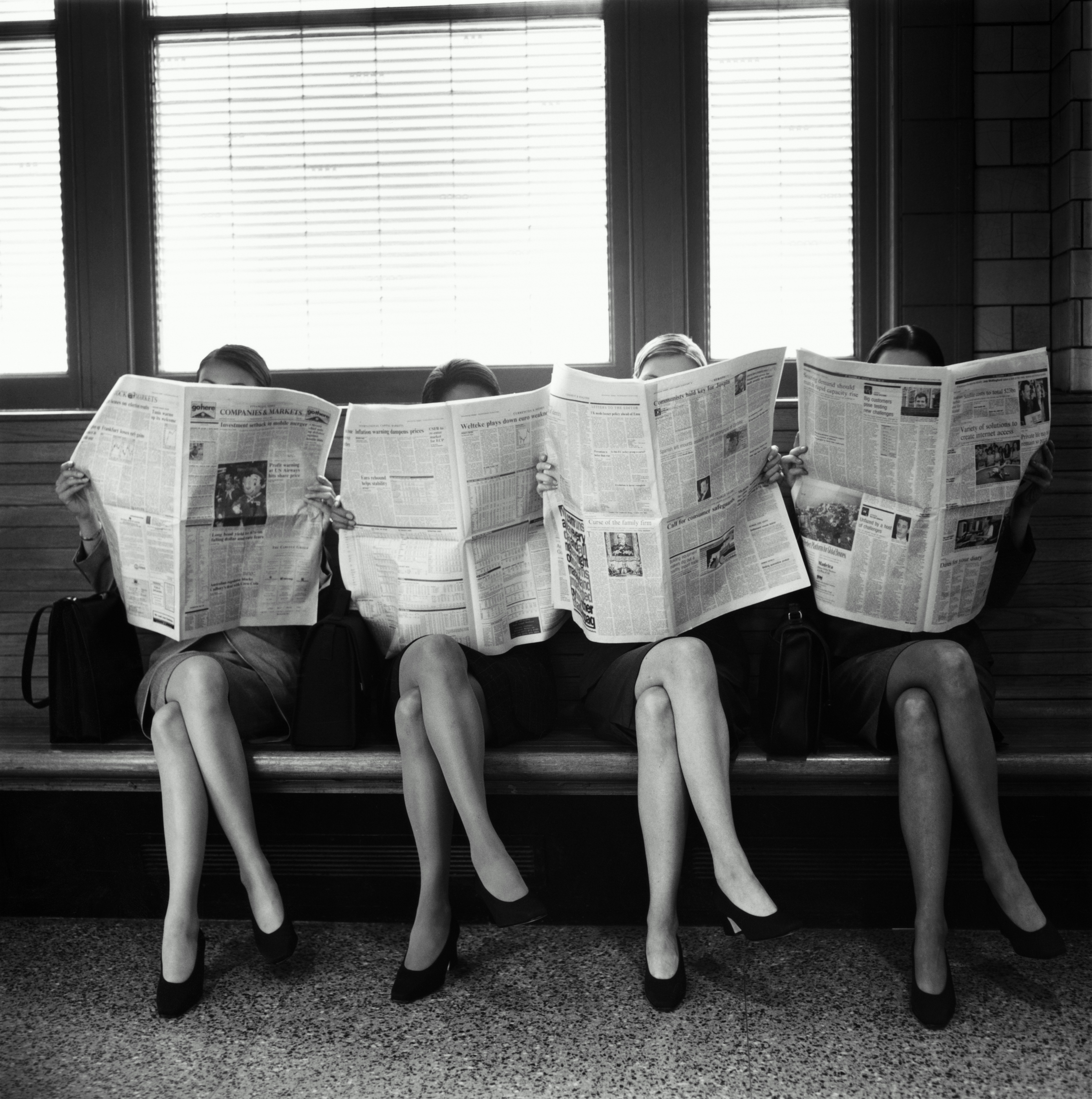 Four businesswomen sitting, reading newspapers, faces covered (B&W)
