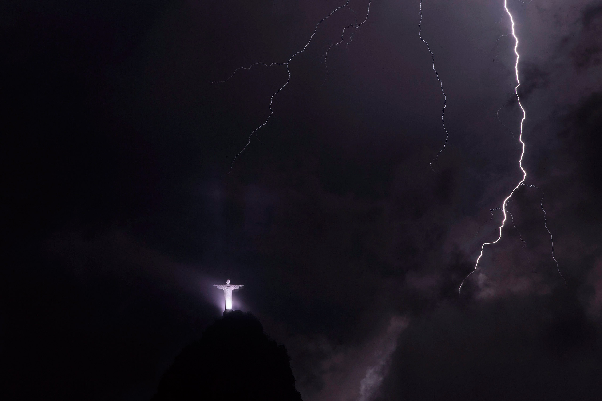 Lightning strikes near The Christ the Redeemer statue atop of Corcovado Mountain during a storm in Rio de Janeiro, Brazil, Feb. 23, 2016.