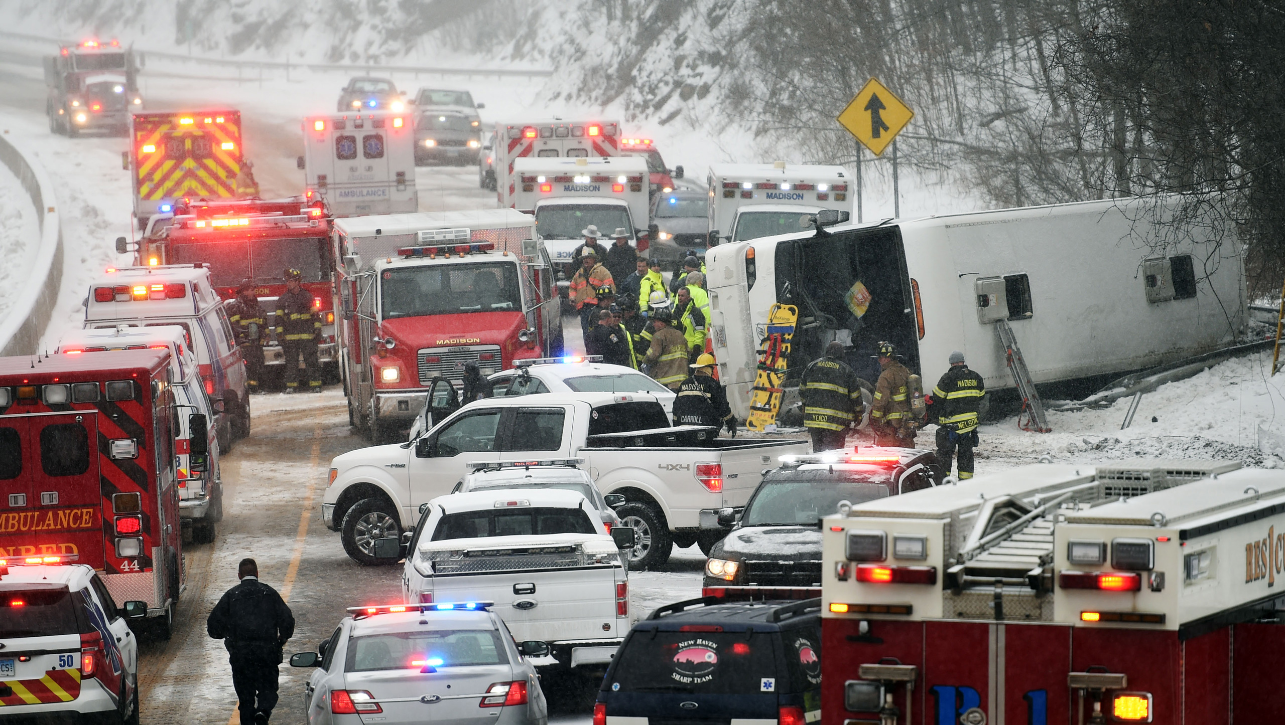 Emergency responders work at the scene of a tour bus rollover on Interstate 95 in Madison, Conn., on Feb. 8, 2016.