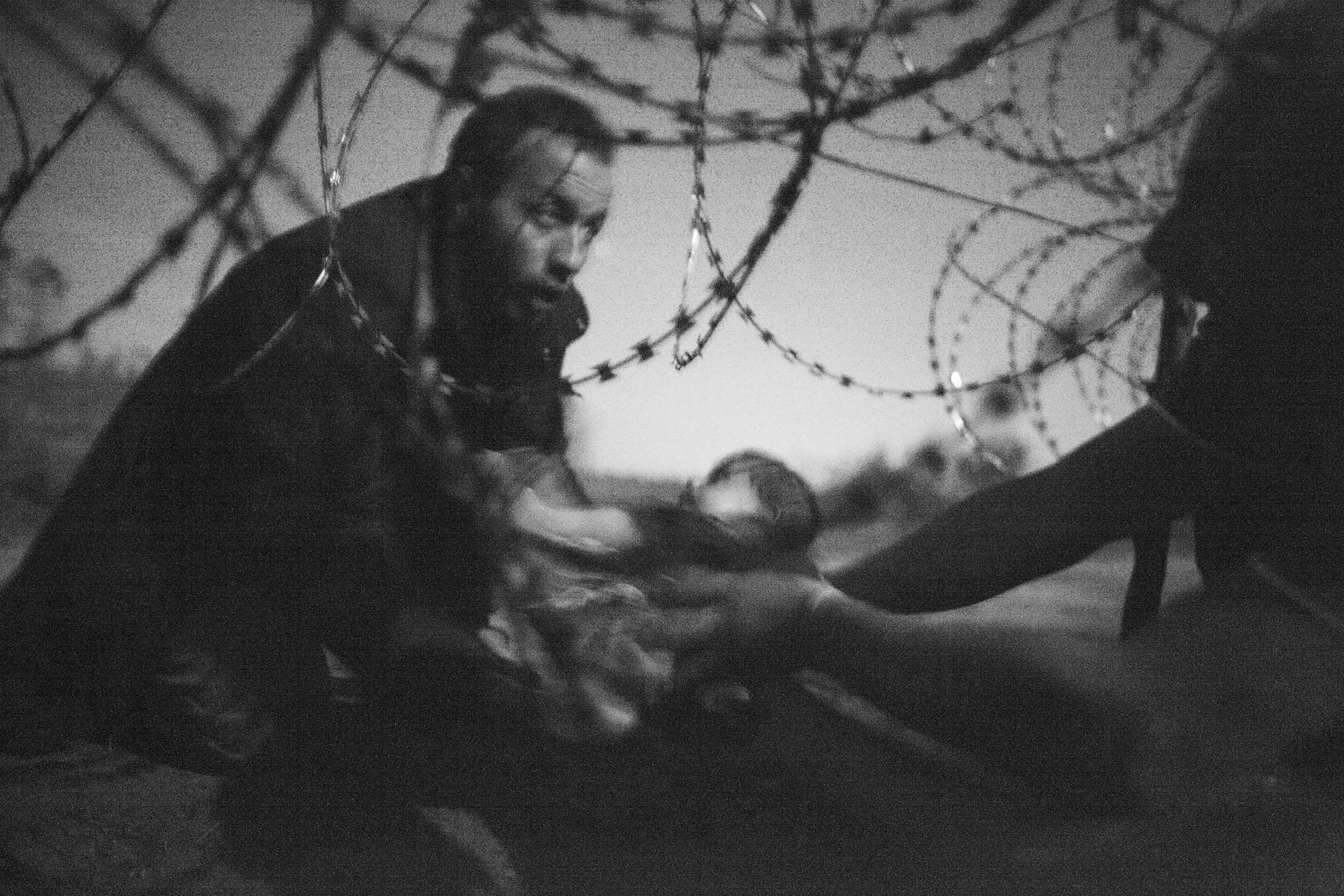 Spot News, 1st prize singles and World Press Photo of the Year. A man passes a baby through the fence at the Hungarian-Serbian border in Röszke, Hungary, Aug. 28, 2015.